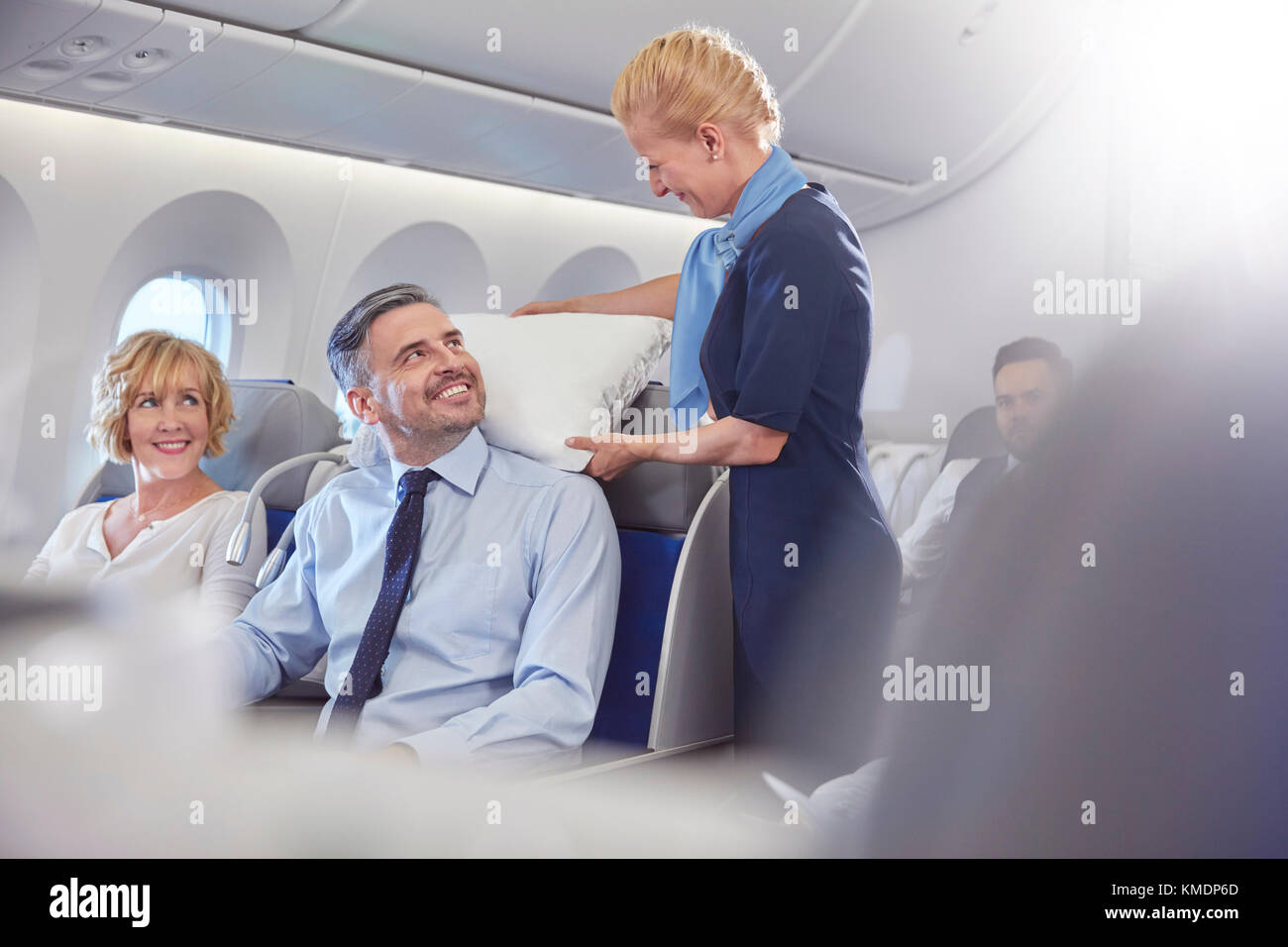 Smiling flight attendant adjusting pillow for businessman in first class on airplane - Stock Image