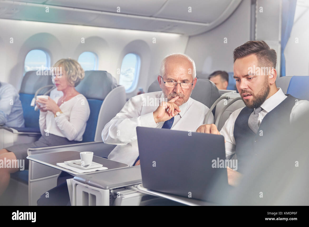 Businessmen working at laptop in first class on airplane - Stock Image