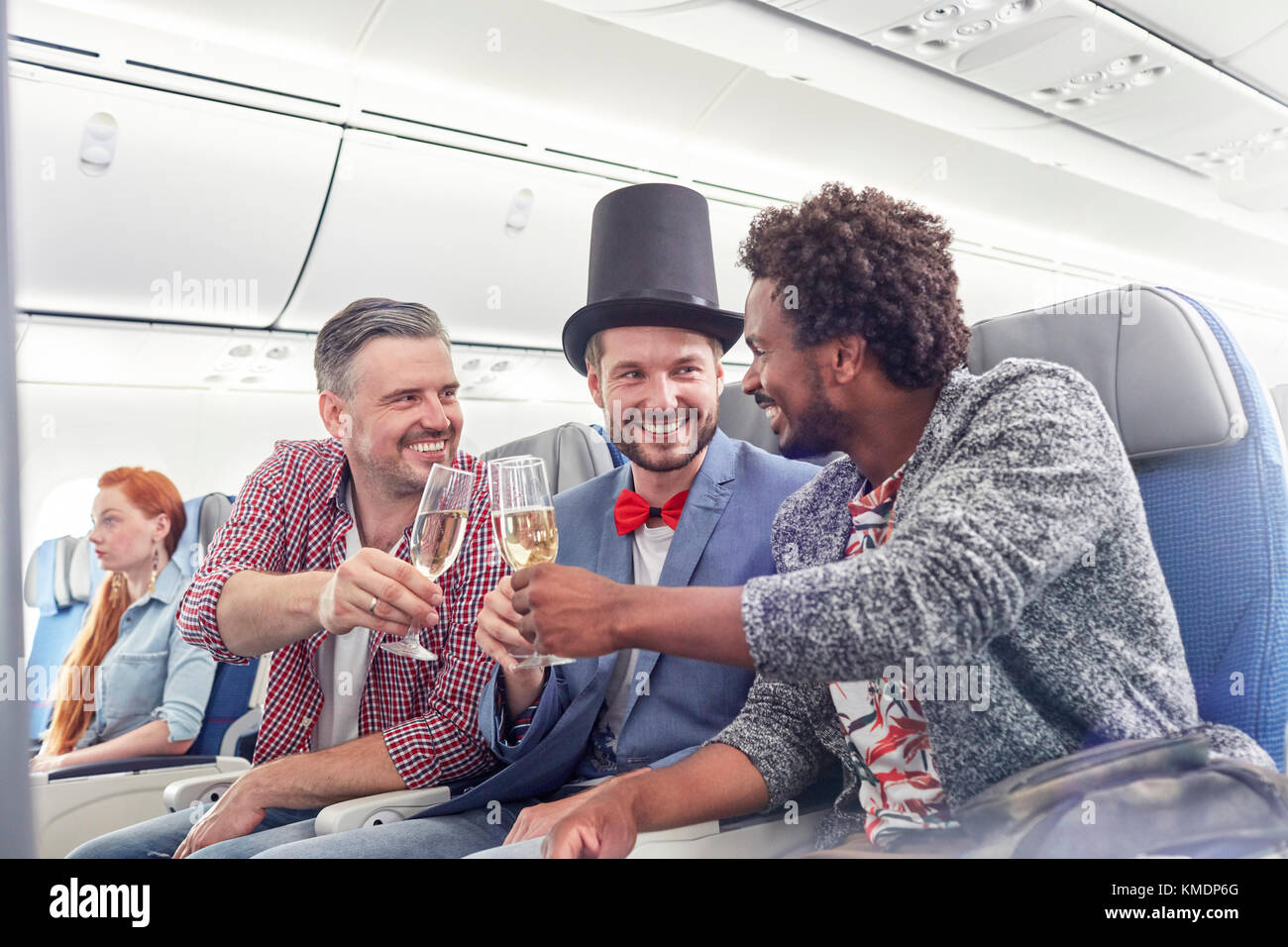 Young male friends toasting champagne glasses in first class on airplane - Stock Image