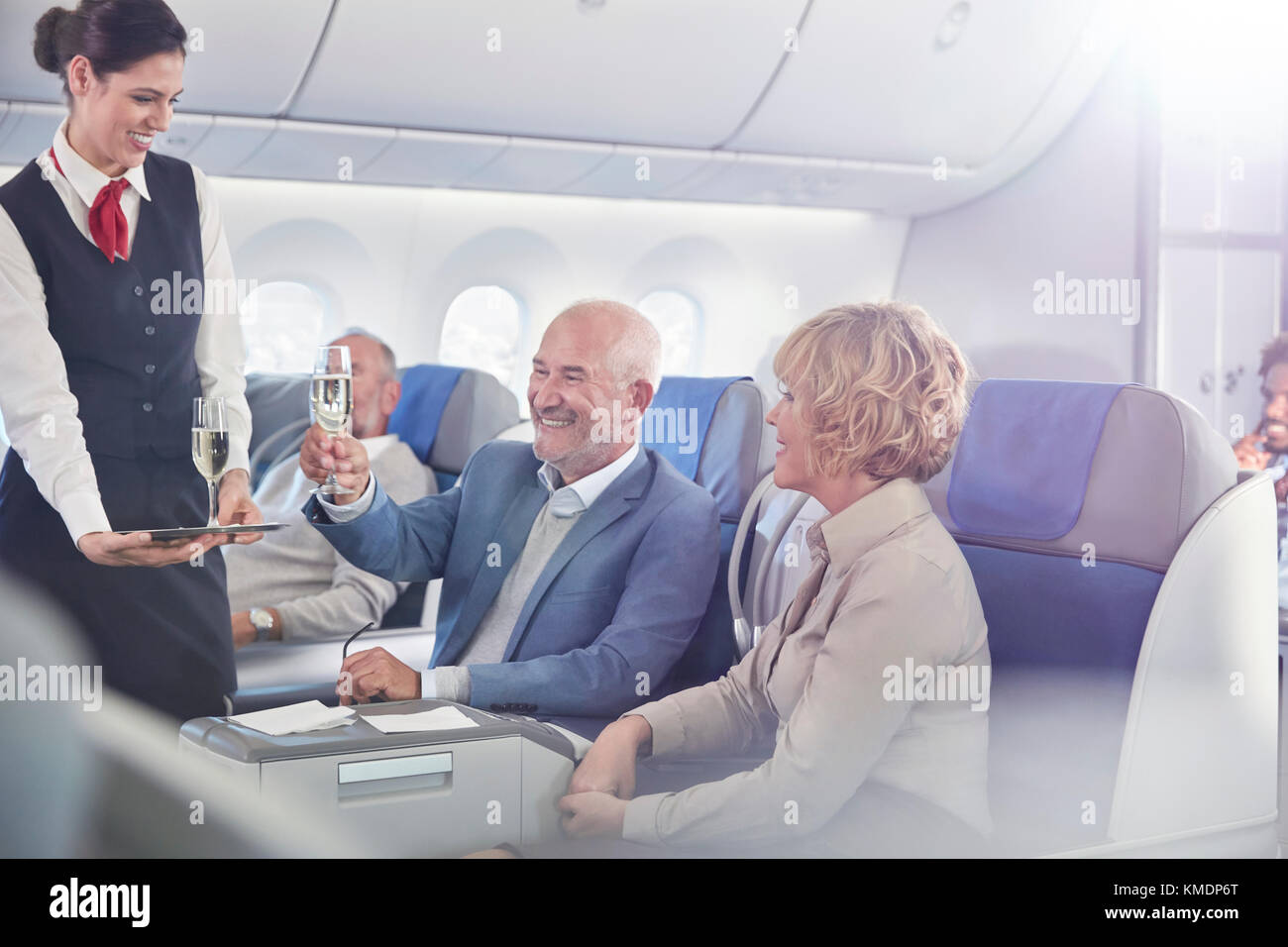 Flight attendant serving champagne to mature couple in first class on airplane - Stock Image