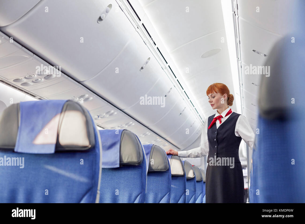 Female flight attendant on empty airplane - Stock Image