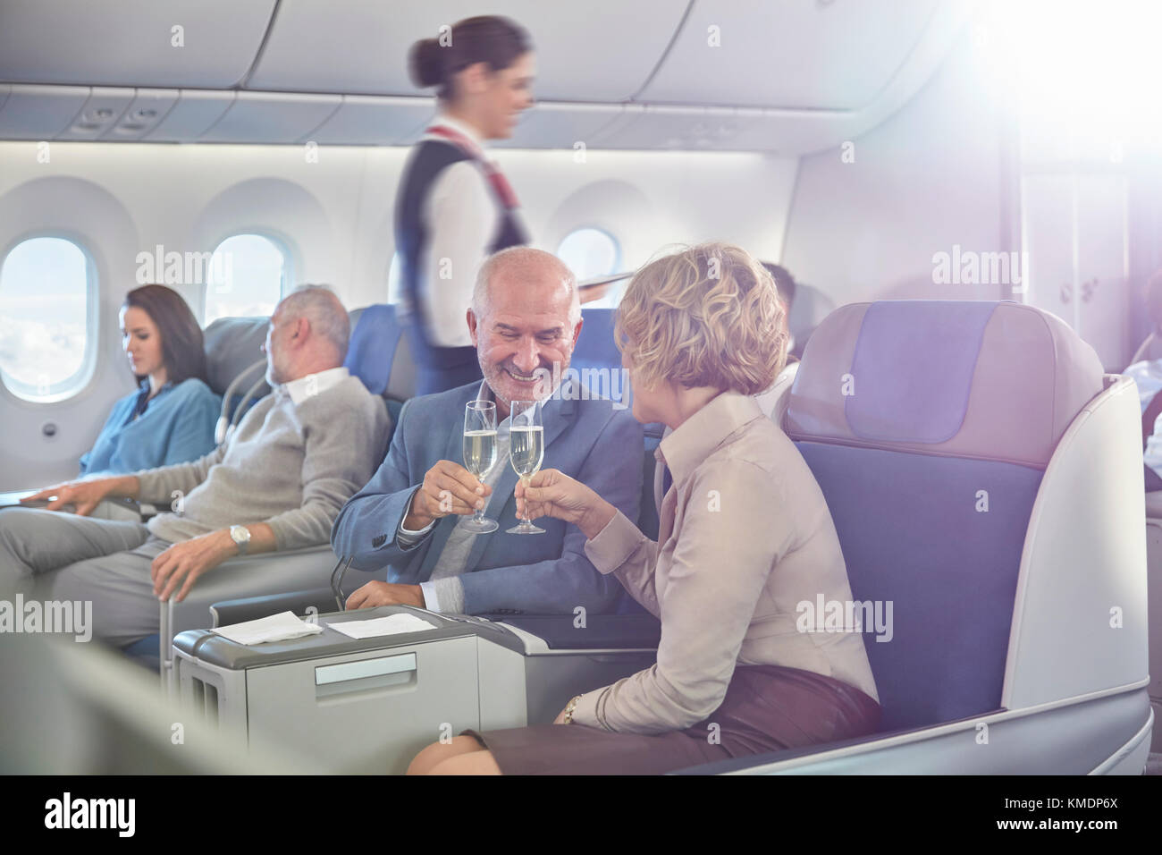 Mature couple toasting champagne glasses in first class on airplane - Stock Image