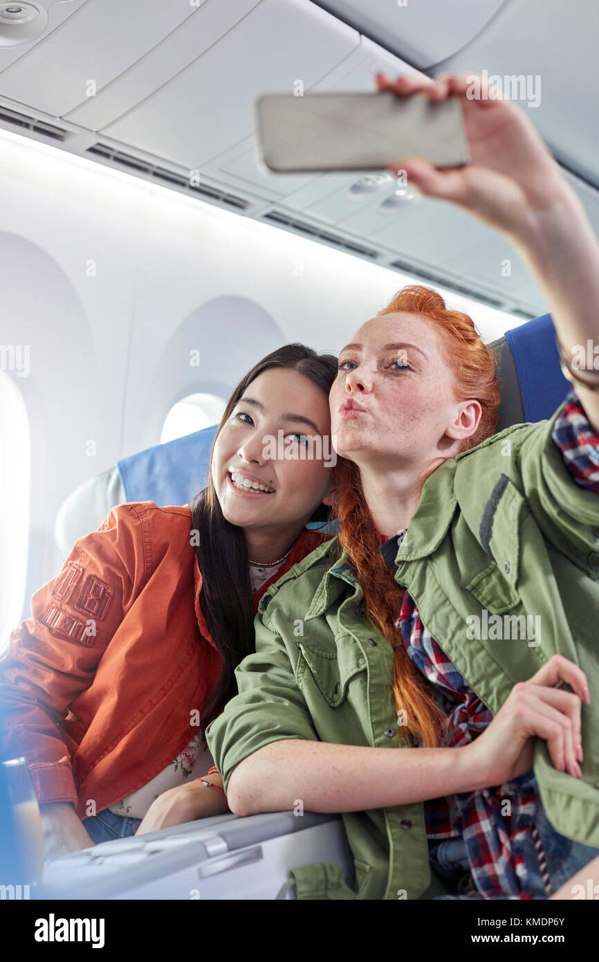 Young women friends with camera phone posing for selfie on airplane - Stock Image
