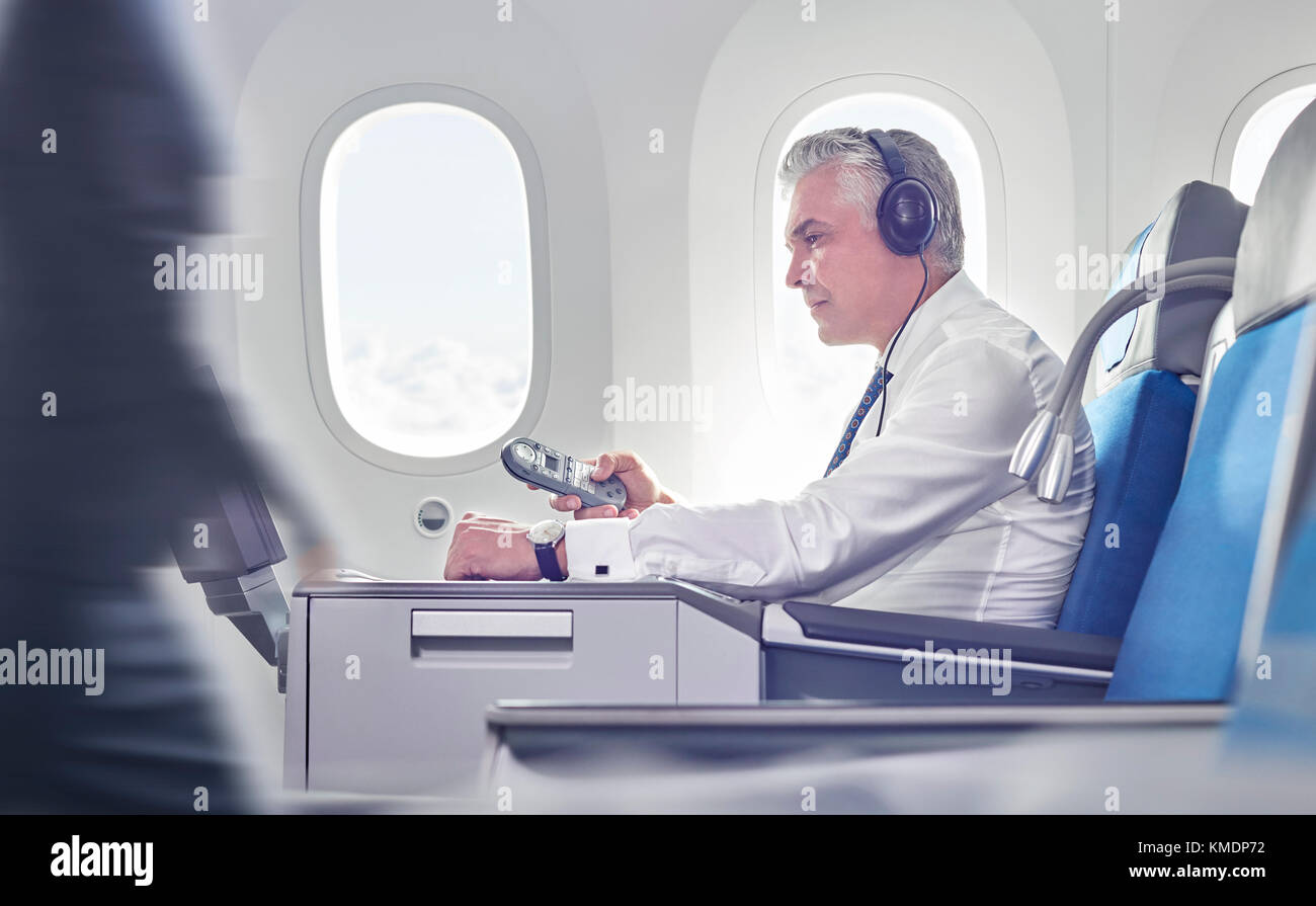 Businessman with headphones and remote control watching movie on airplane - Stock Image