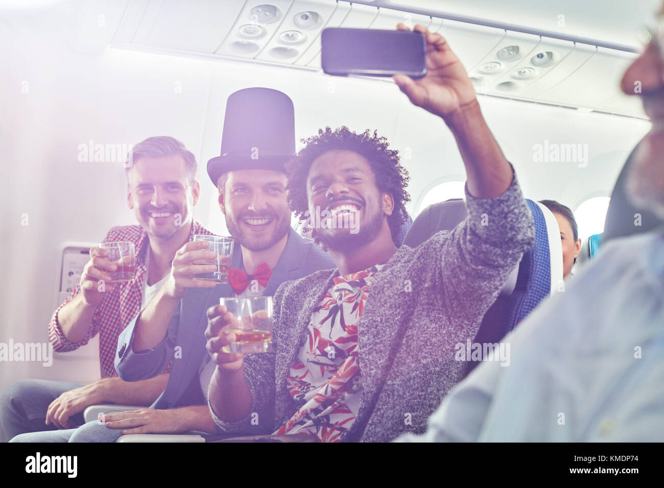 Enthusiastic young male friends with camera phone drinking and taking selfie on airplane - Stock Image