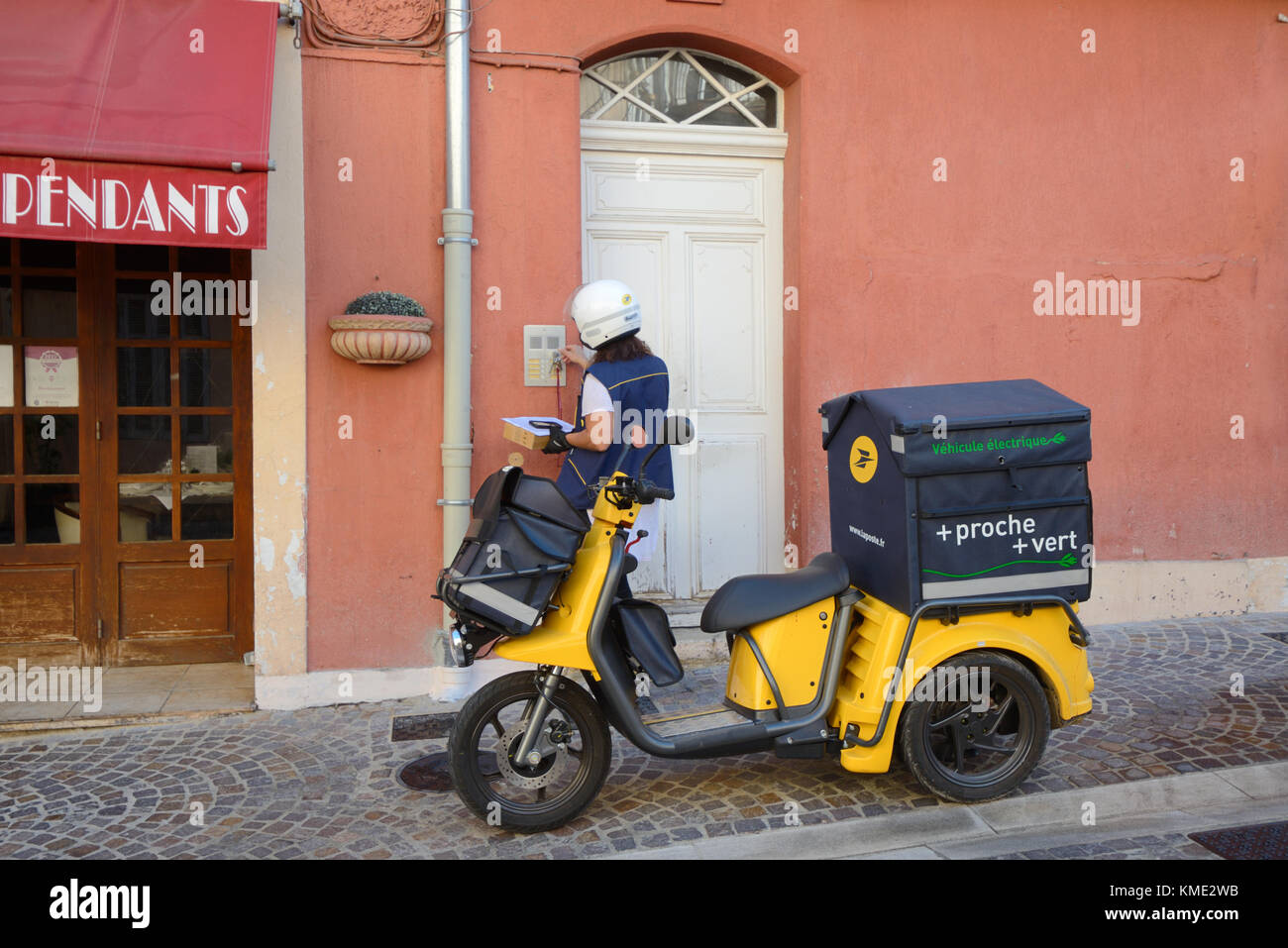 French Postman or Postal Worker Delivering Letters Using Electric Tricycle in Le Suquet Old Town, Cannes, Alpes - Stock Image