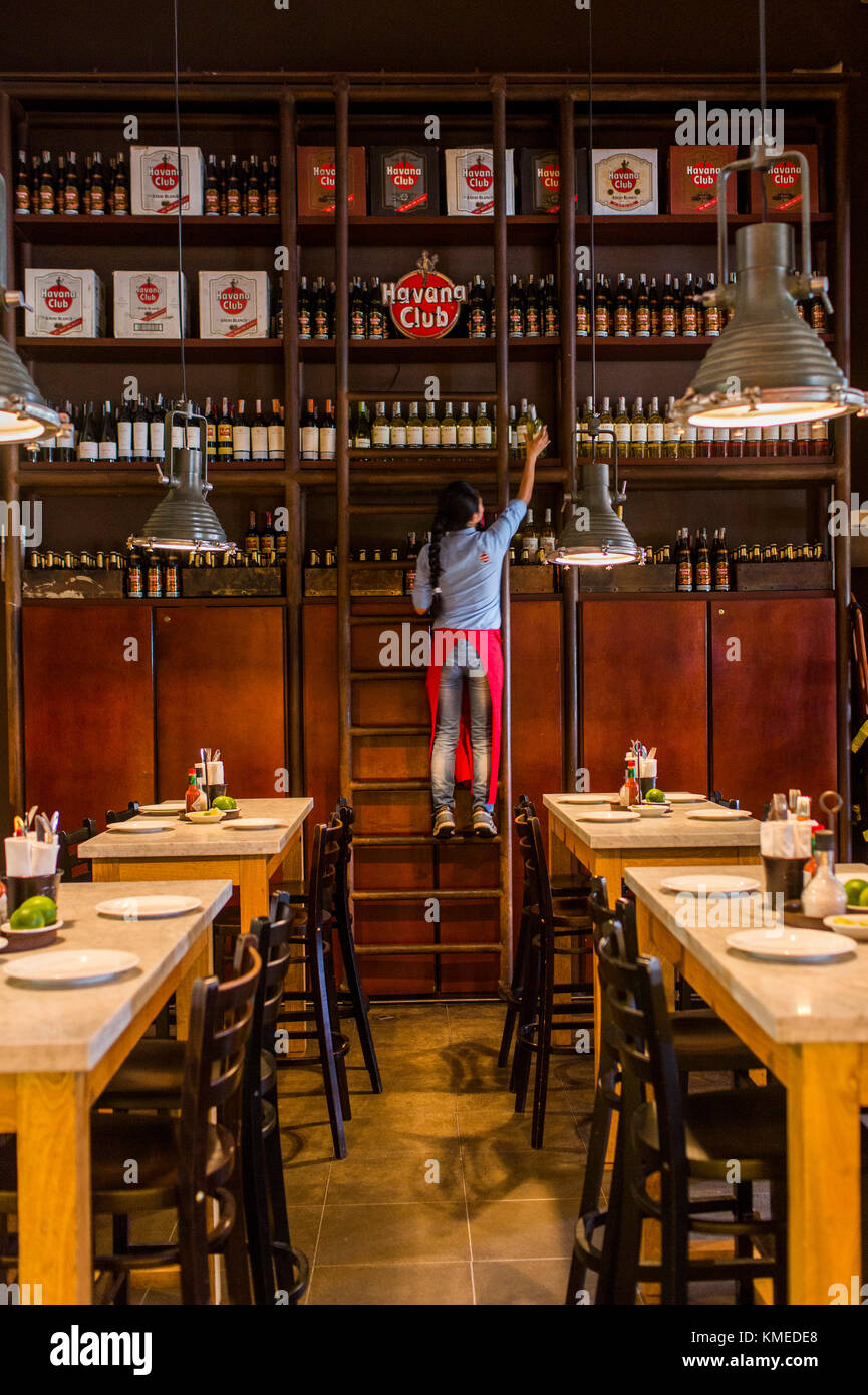 Woman pulling down bottle of rum at Central de Cevicheria, restaurant in Bogota, Colombia - Stock Image