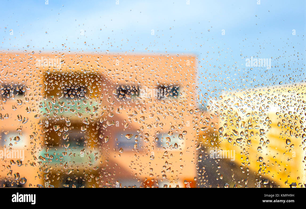 Rain drops on the glass in the background blurred flat building - Stock Image