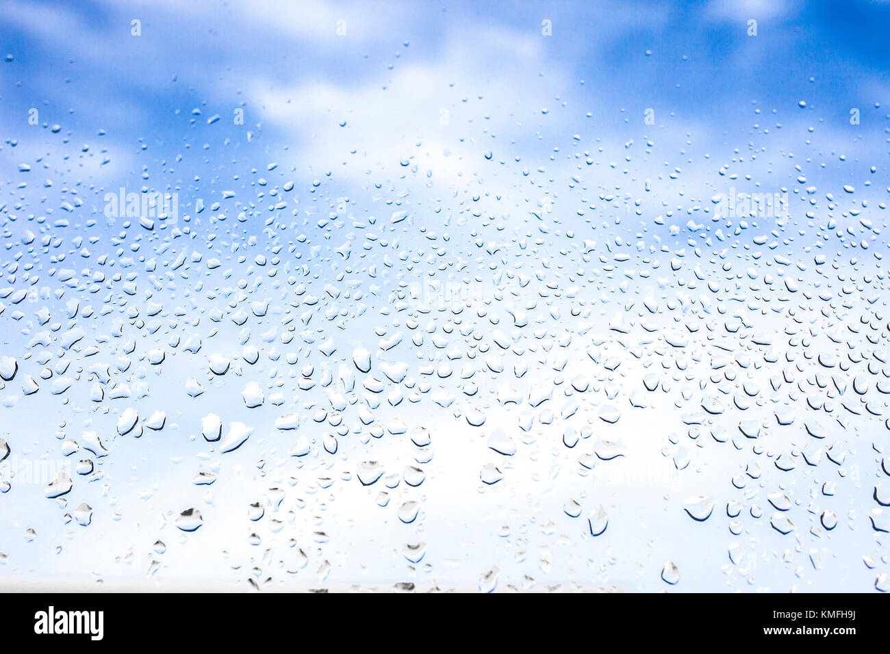 Rain drops on the glass in the background blurred blue cloudy sky. After raining concept - Stock Image
