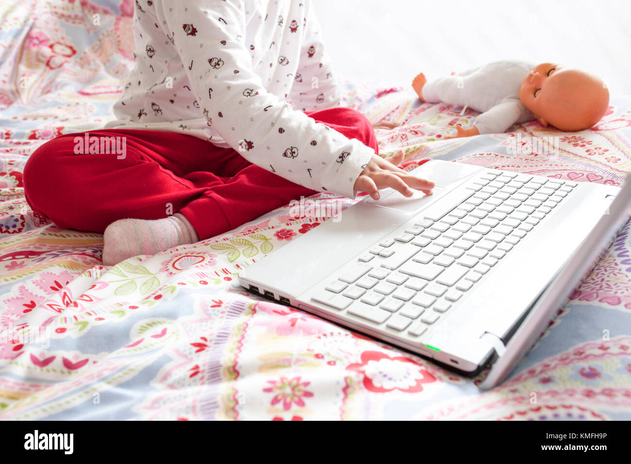 Little girl sitting in bed and surfing on Internet in her bedroom. Parental control concept - Stock Image