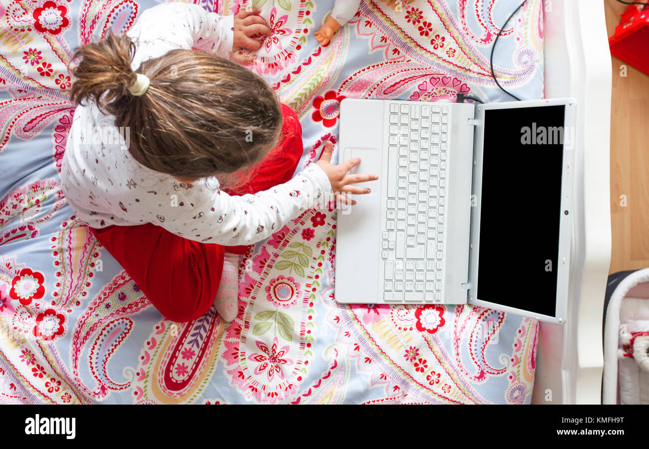 Little girl sitting in bed and playing online games in her bedroom. High angle view - Stock Image