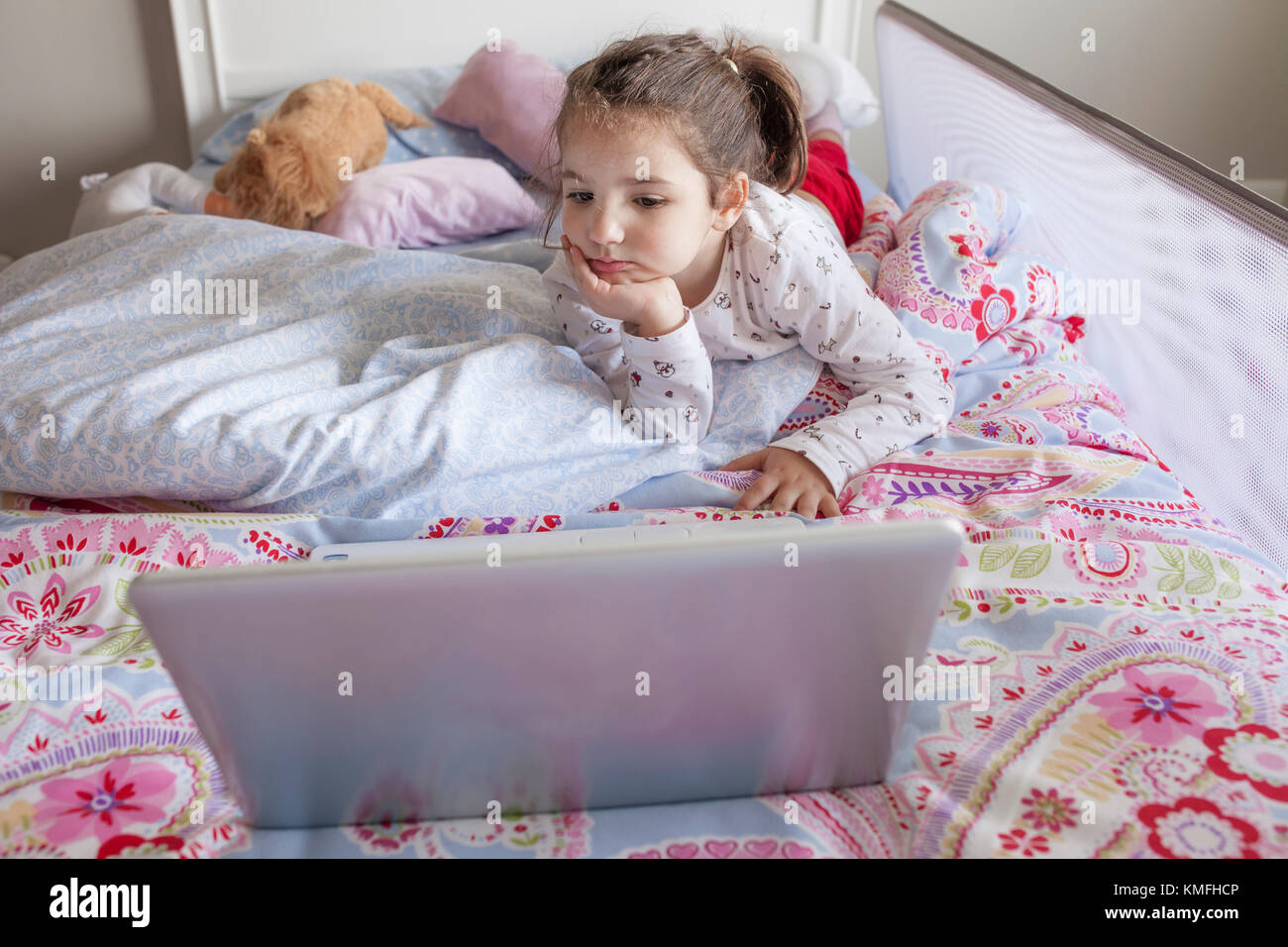 Little girl lying in bed and watching cartoons with a laptop in his bedroom. She looks entertained - Stock Image