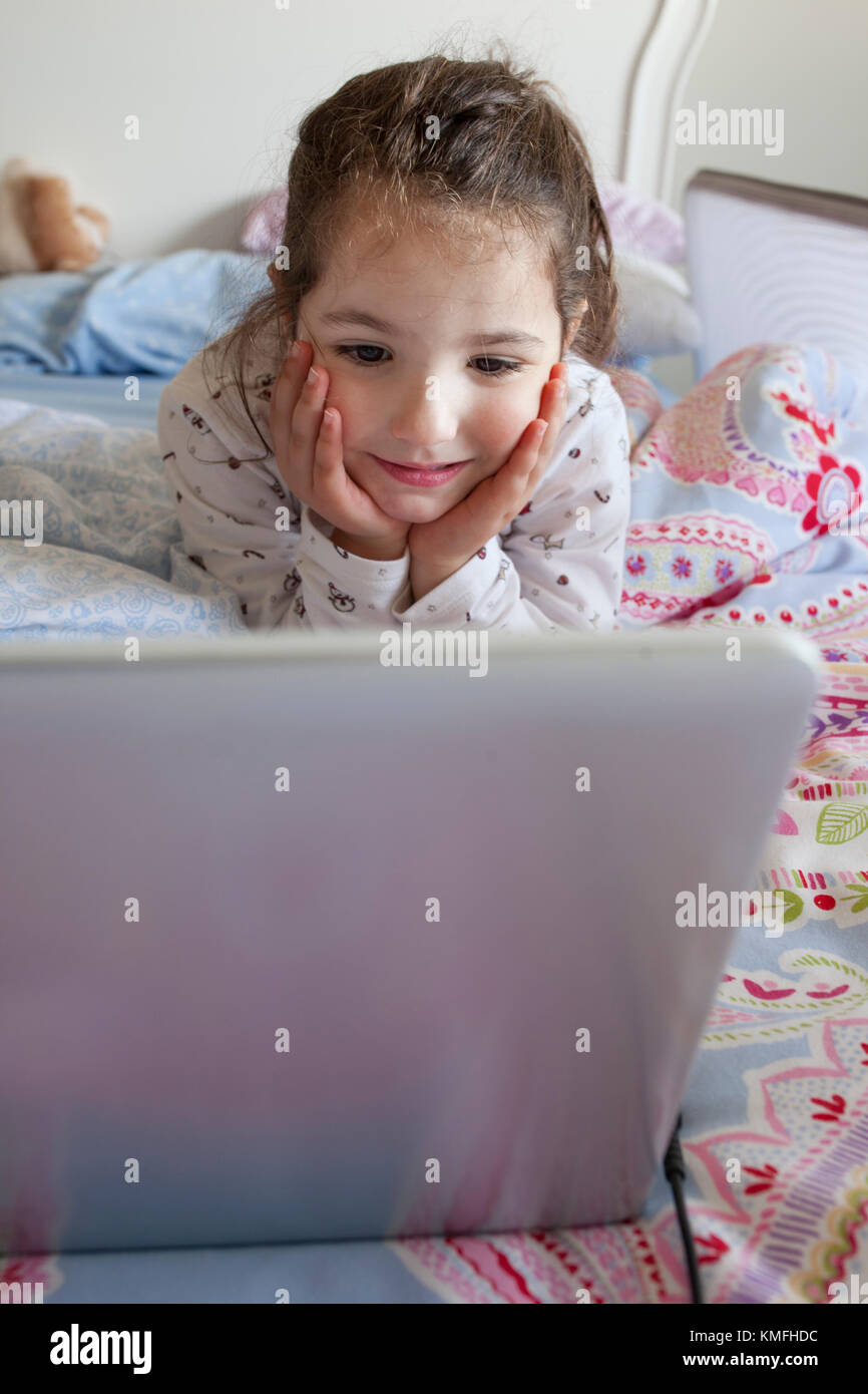 Little girl lying in bed and playing with a laptop in his bedroom. She looks having fun - Stock Image