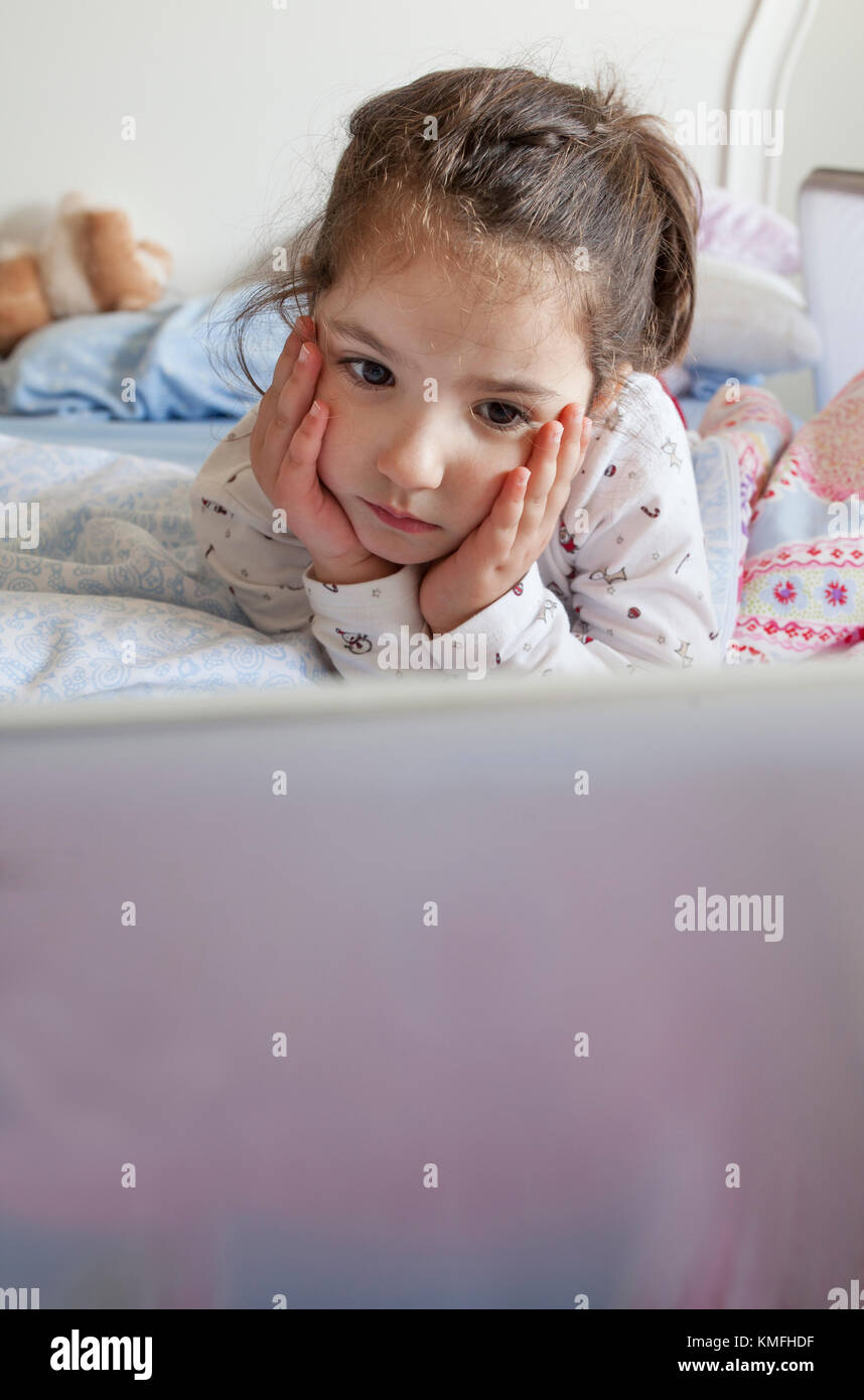 Little girl lying in bed and playing with a laptop in his bedroom. She looks attentive - Stock Image