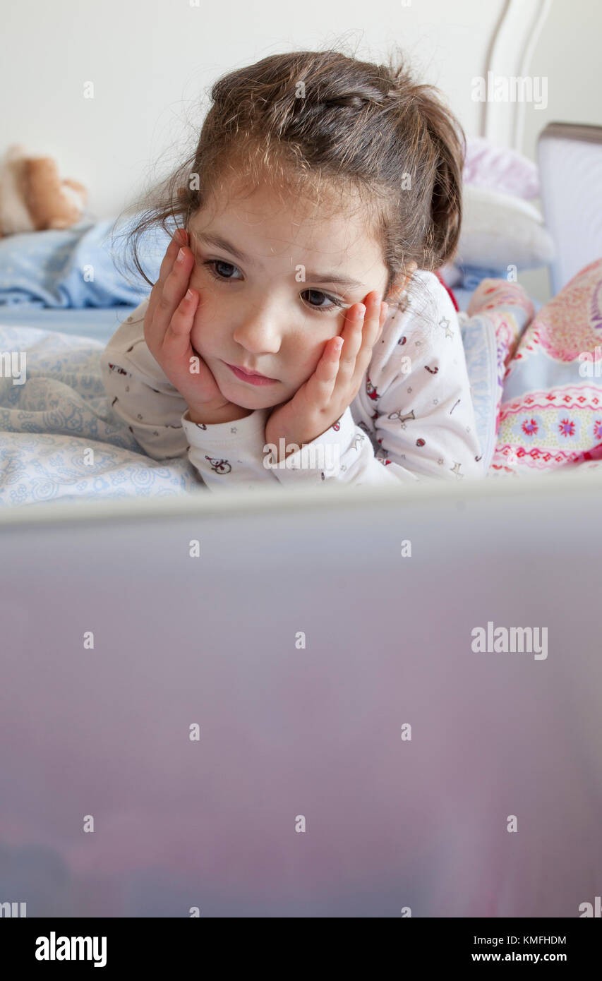 Little girl lying in bed and playing with a laptop in his bedroom. She looks inattentive - Stock Image