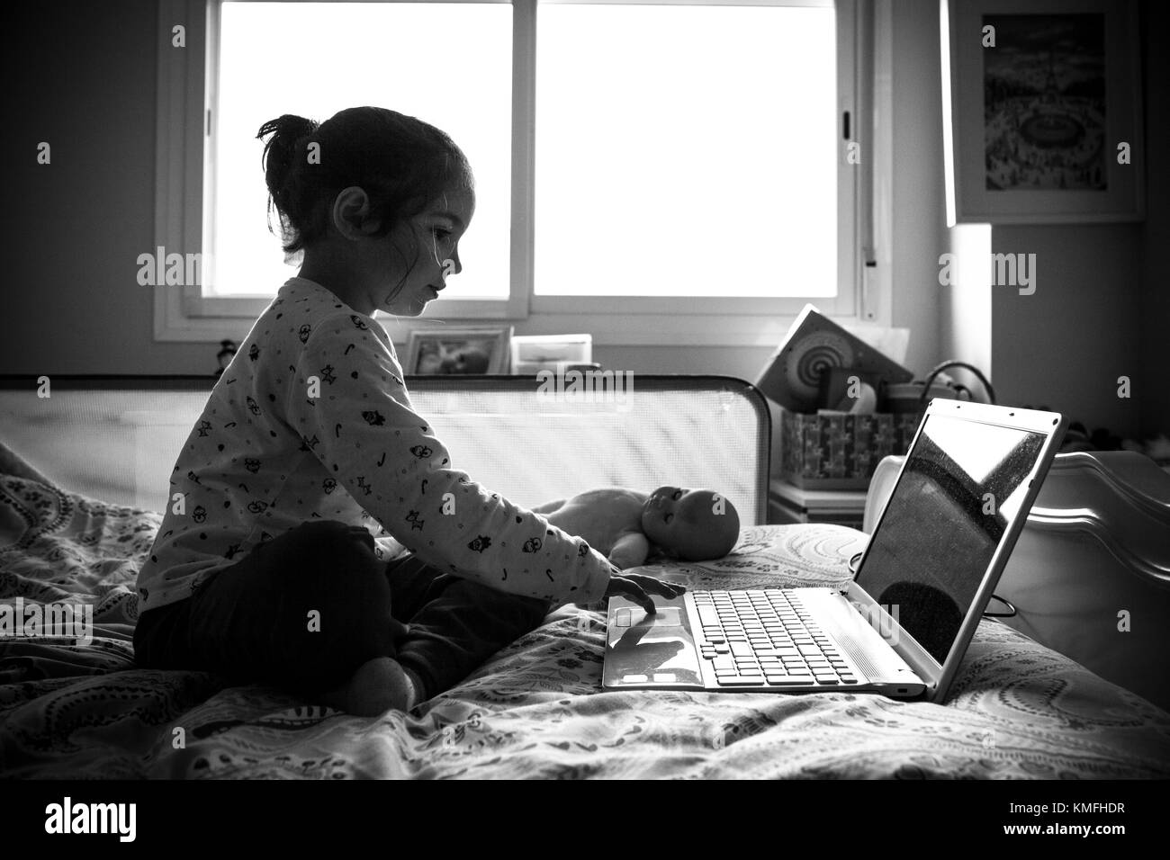 Little girl sitting in bed and playing online games in his bedroom. Black and white shot - Stock Image