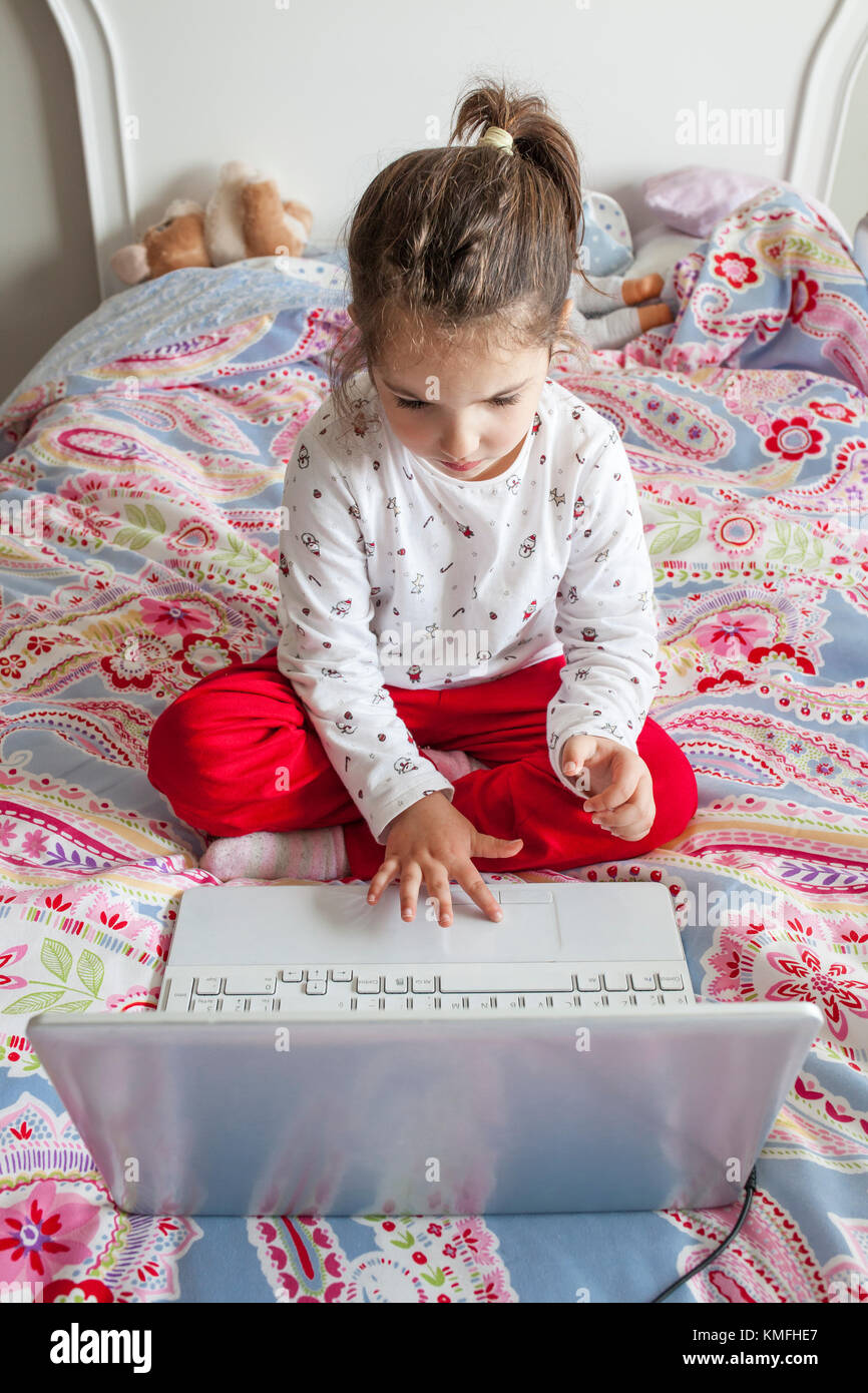 Little girl sitting in bed and playing online games with laptop computer - Stock Image