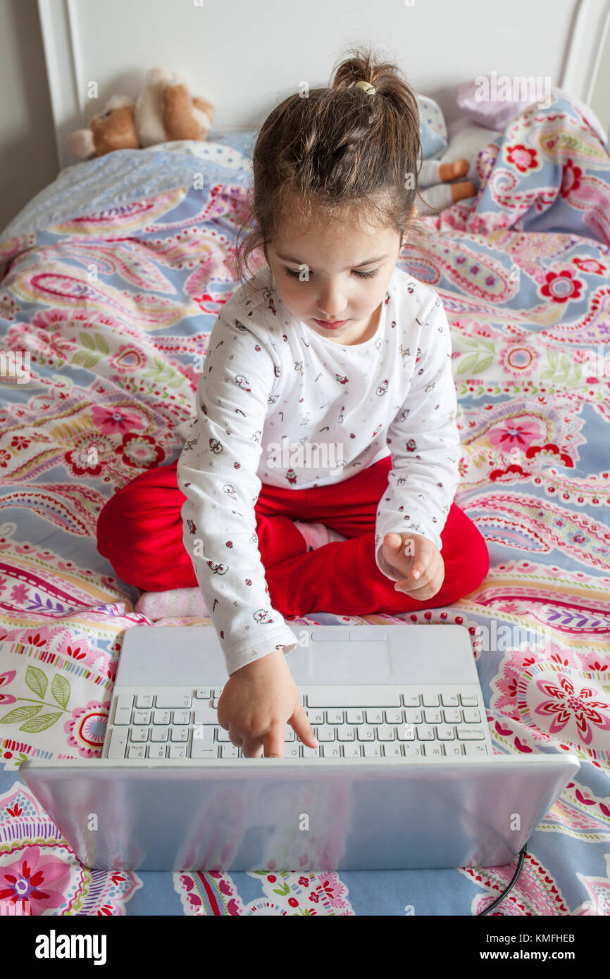 Little girl sitting in bed and playing online games with laptop computer. She is touching the screen - Stock Image