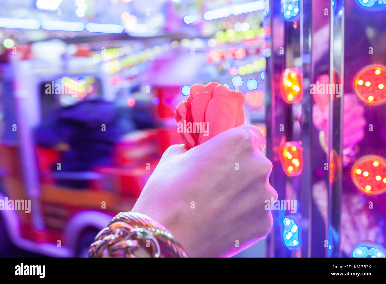 Woman hand with a fistfull of chips for fair ground ride childrens cars track. Night scene - Stock Image