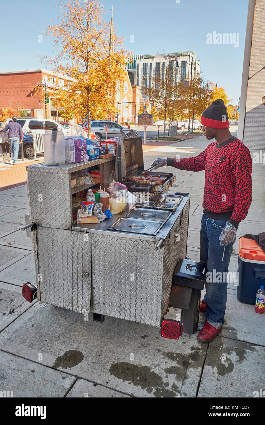 Black male, African American, selling hotdogs from his cart on a city sidewalk. - Stock Image