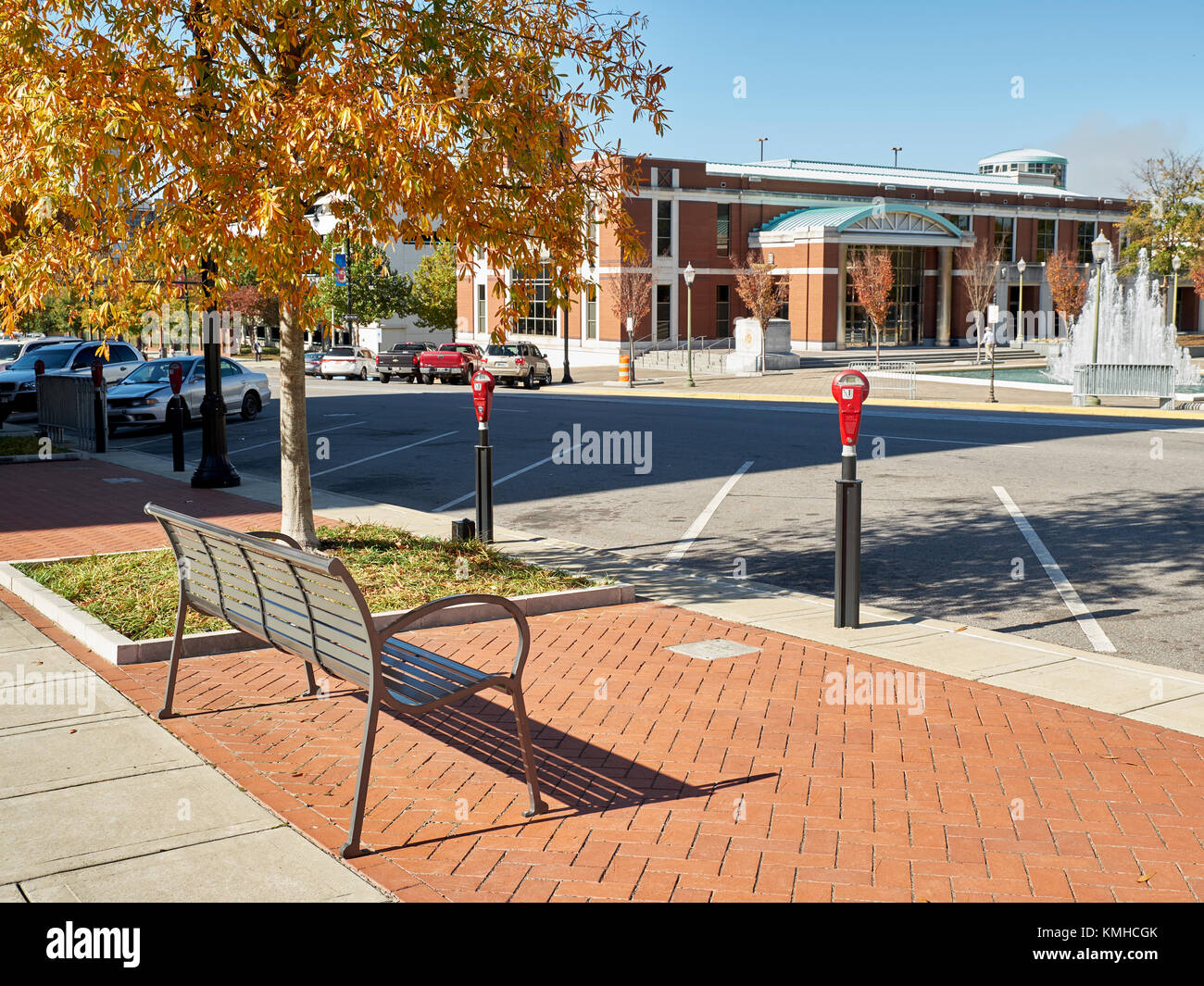 Empty parking spaces and a metal bench on a street in the downtown district of a city. - Stock Image