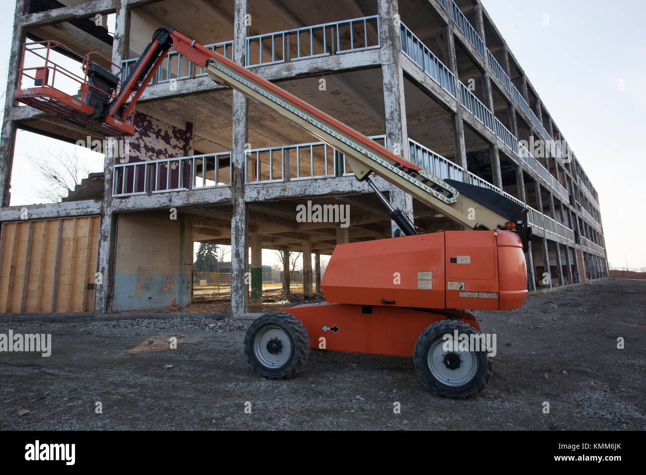 Boom Lift parked on Construction Site with boom raised - Stock Image