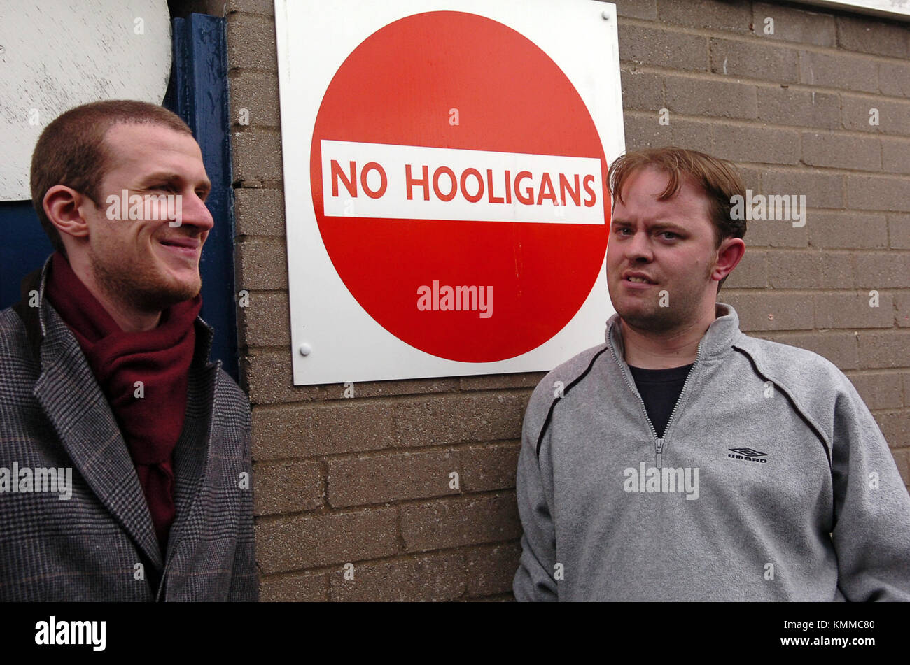 Sports journalist chatting next to 'No Hooligans' sign banning hooligans from Cardiff City Football Club - Stock Image