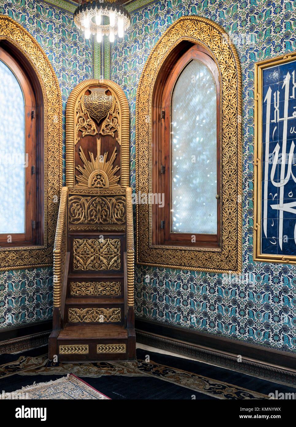 Golden ornate minbar, wooden arched window framed by golden ornate floral pattern, and floral blue pattern ceramic - Stock Image