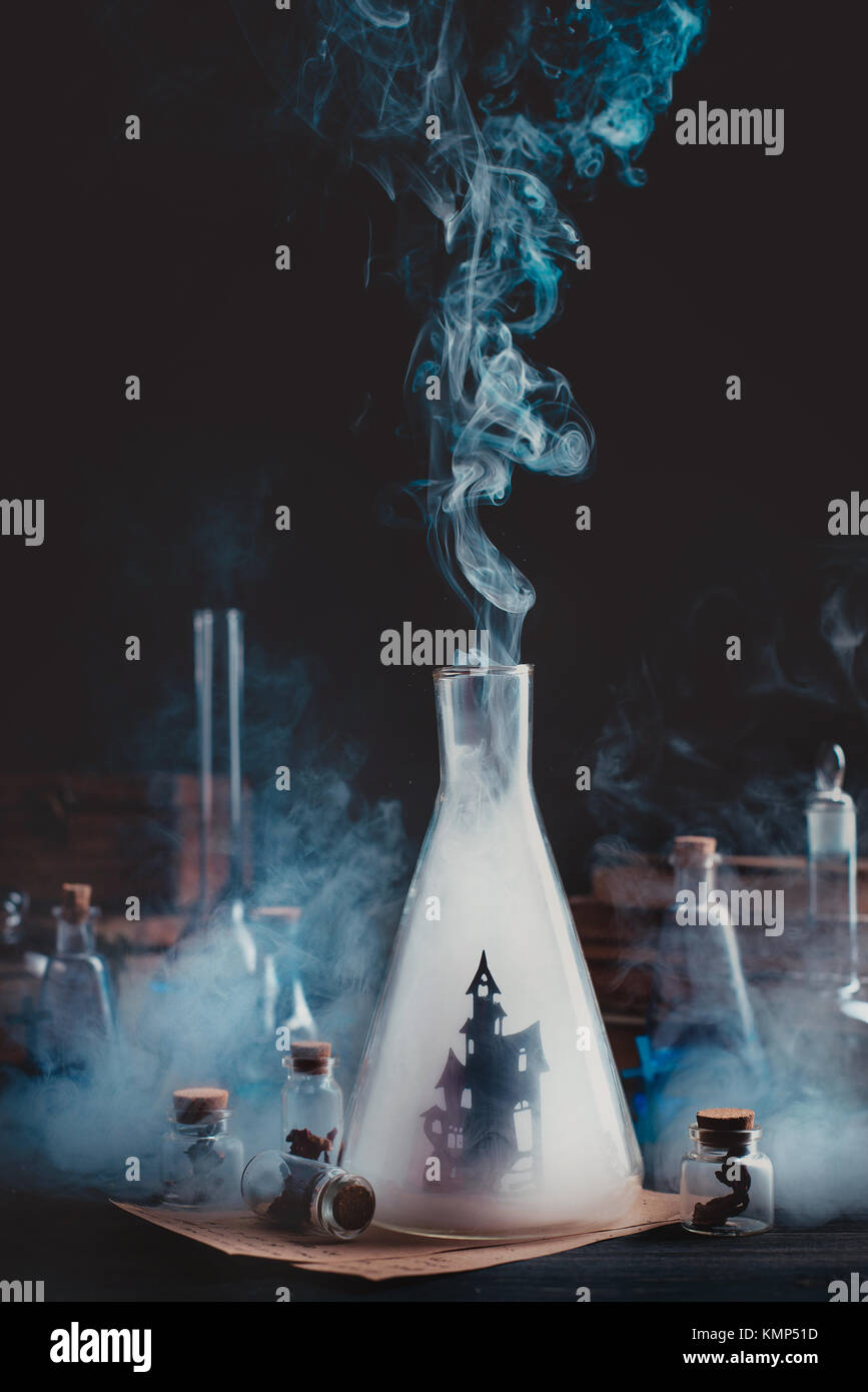 Lab bottle with haunted castle silhouette. Wizard workplace with smoke and magical equipment. Dark conceptual still - Stock Image
