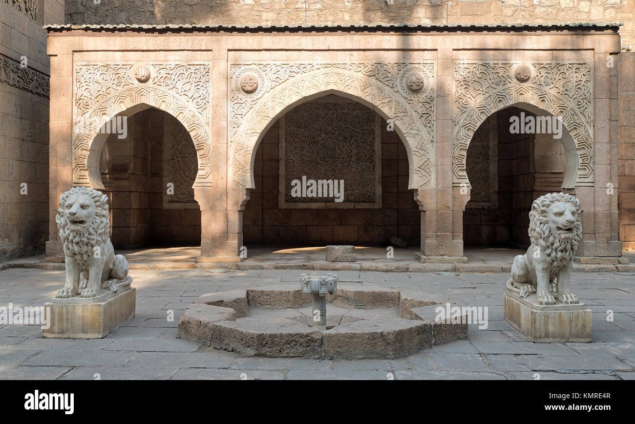 Two white marble lions statues and decorative fountain in front of three adjacent decorated stone arches at the - Stock Image