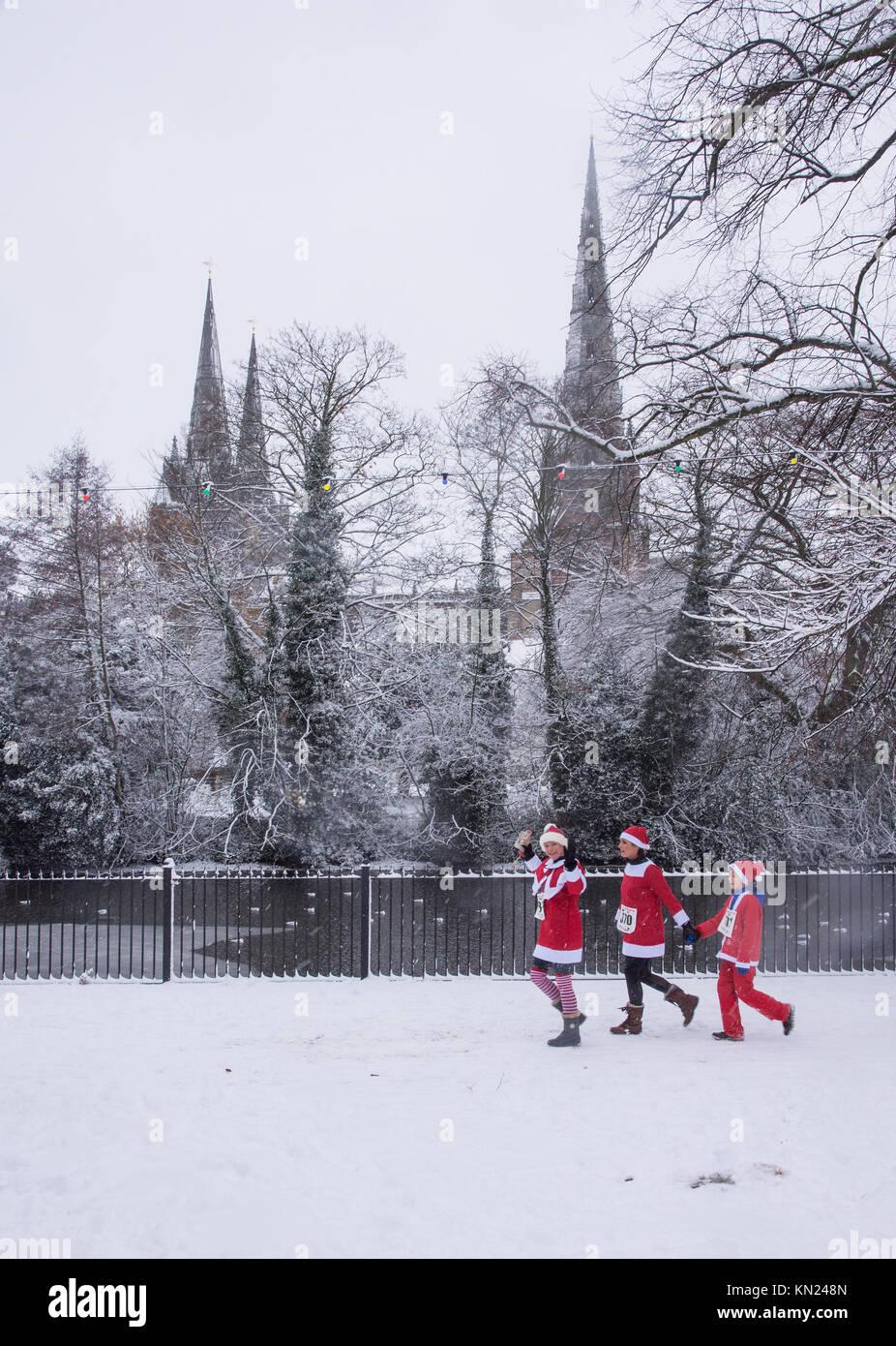 Lichfield, UK. 10th Dec, 2017. Three participants in the Lichfield Santa Dash run along Minster Pool with Lichfield - Stock Image