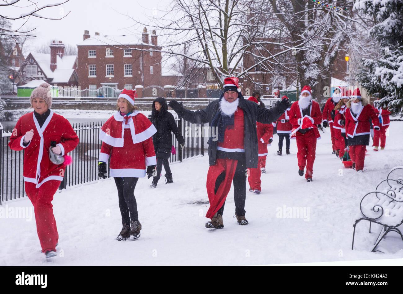 Lichfield, UK. 10th Dec, 2017. People taking part in the Lichfield Santa Dash go past Minster Pool dressed in Santa - Stock Image