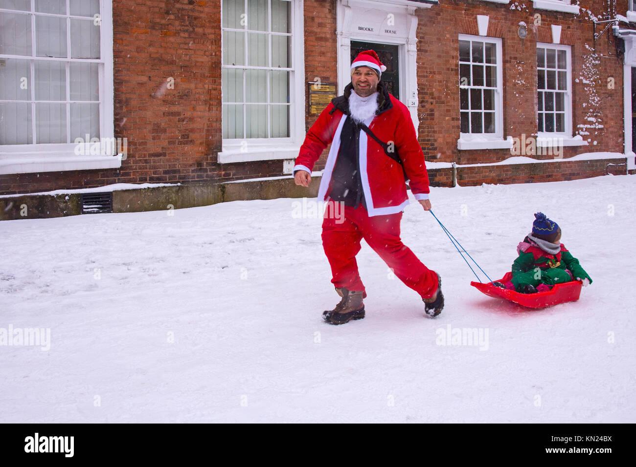 Lichfield, UK. 10th Dec, 2017. A happy father tows his child on a sledge in the Lichfield Santa Dash in Dam Street - Stock Image