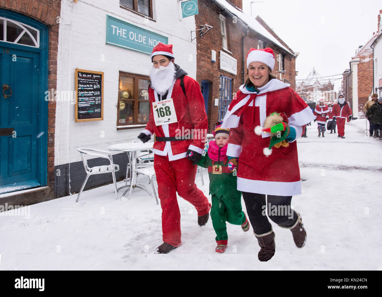 Lichfield, UK. 10th Dec, 2017. A father, mother and in the Lichfield Santa Dash running in Dam Street dressed in - Stock Image