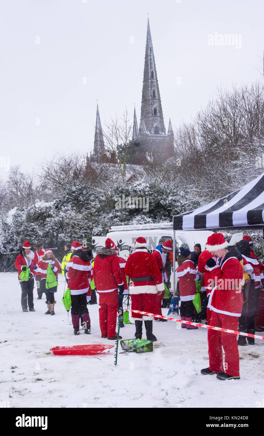Lichfield, UK. 10th Dec, 2017. Competitors dressed in a Santa Claus Father Christmas suits relax at the end of the - Stock Image