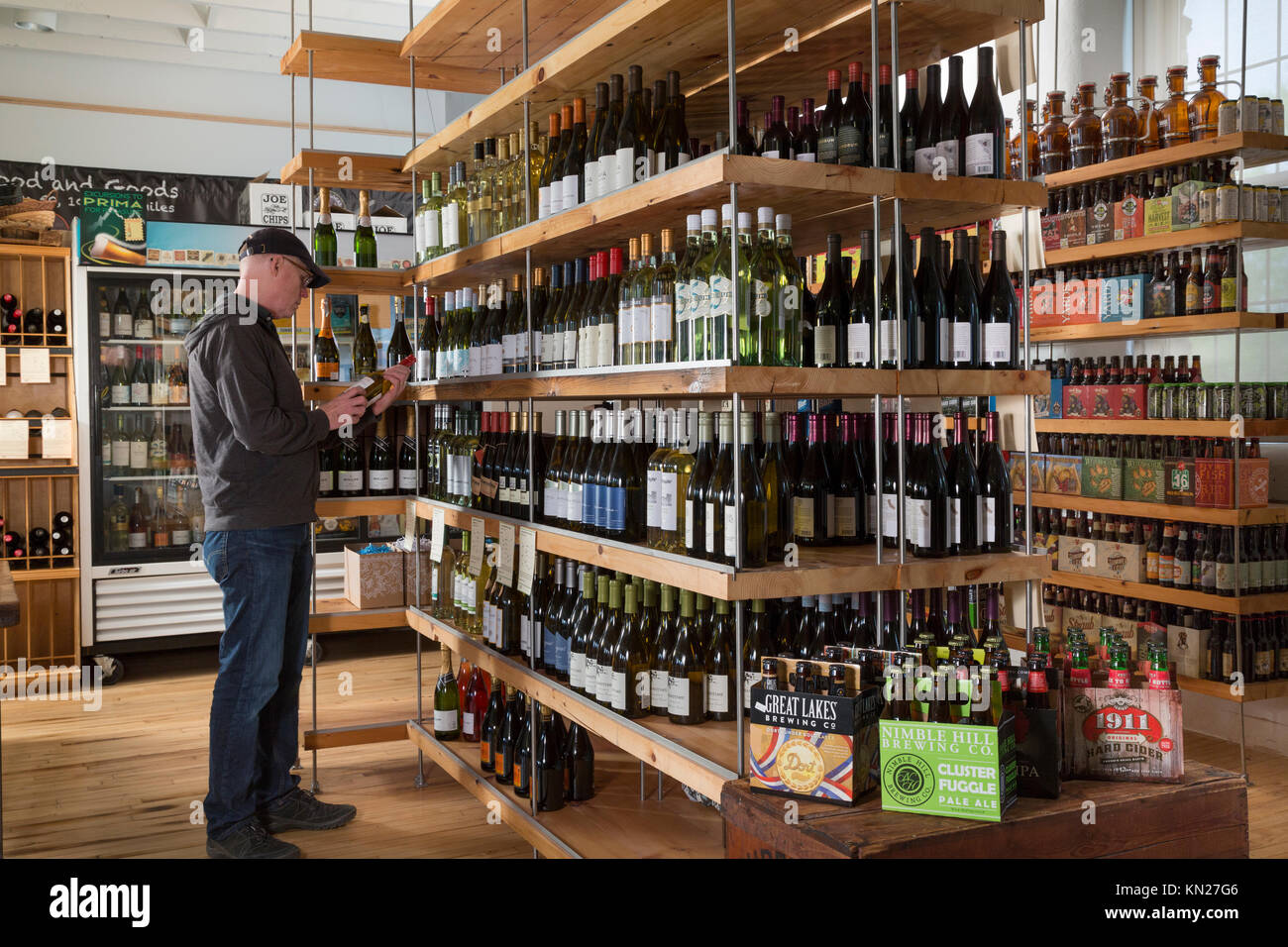 Man selecting Wine and Beer at small grocery, The Mill Market, Hawley, Pennsylvania, USA, - Stock Image