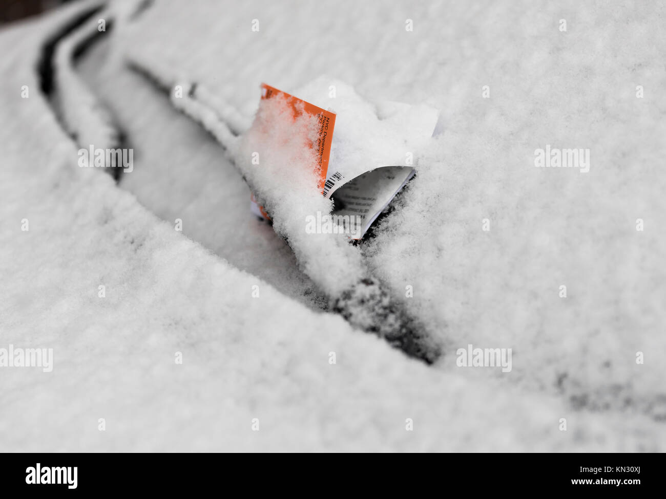 Parking violation ticket on snow covered car windshield - Stock Image