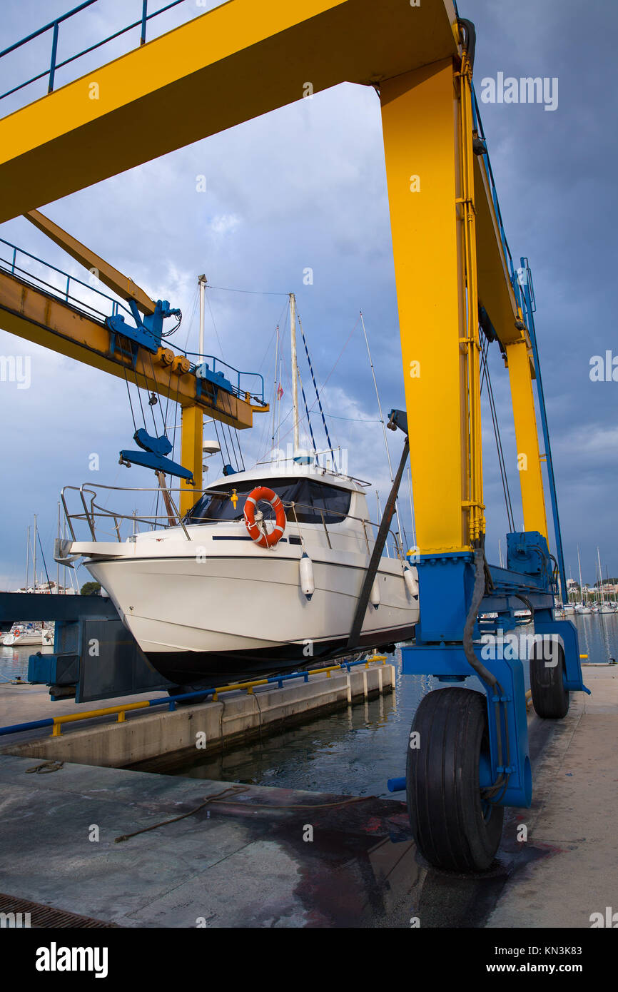 Boat wheel crane elevating motorboat to yearly paint task. - Stock Image