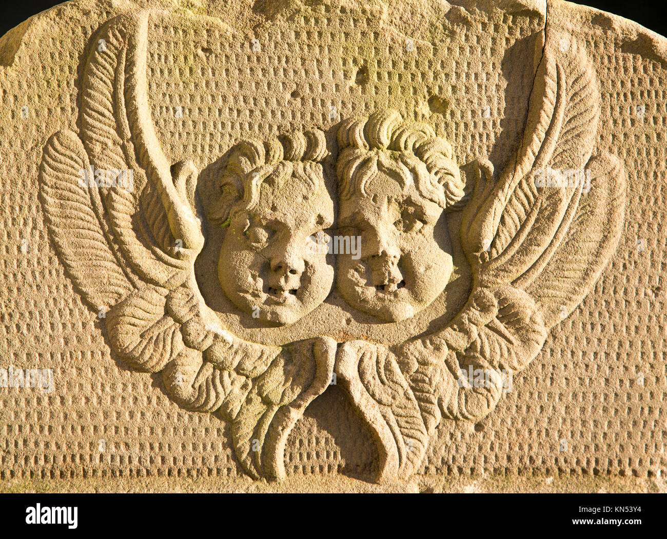 Two angel faces and wings on stone gravestone in church graveyard, Suffolk, England, UK - Stock Image
