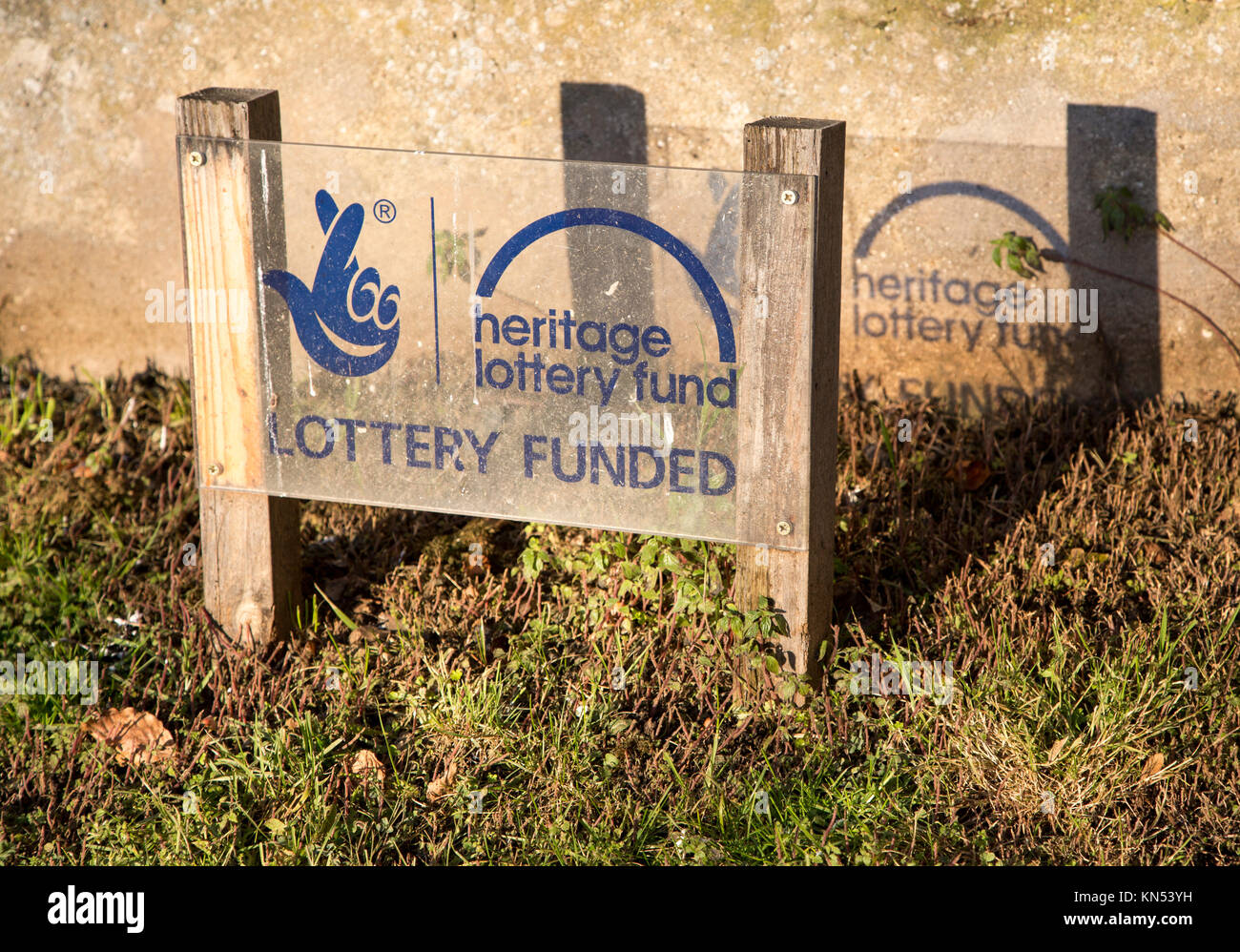 Sign in front of wall showing funding from Heritage National Lottery Fund, Suffolk, England, UK - Stock Image