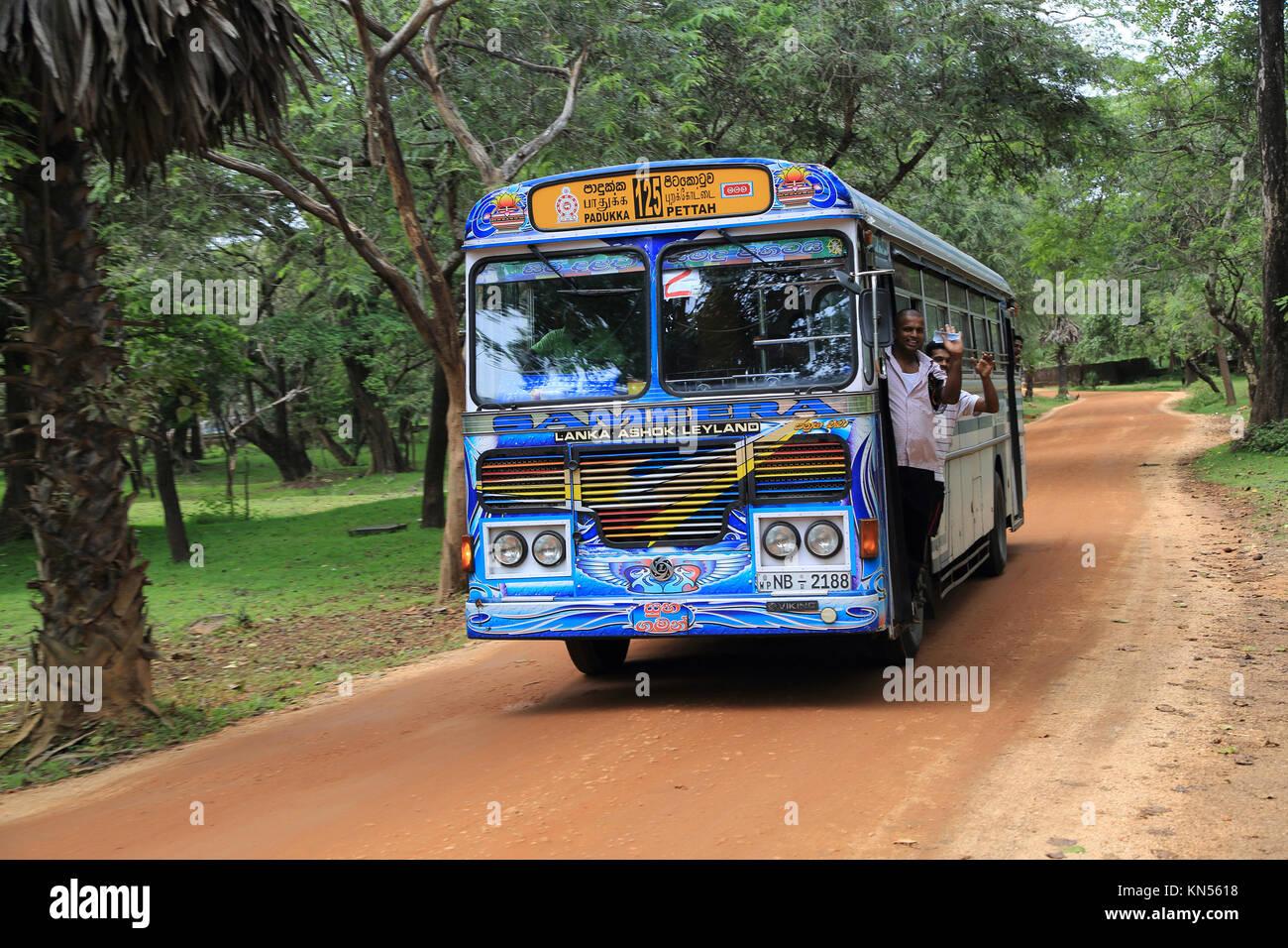 Colourful Lanka Ashok Leyland bus, Polonnaruwa, North Central Province, Sri Lanka, Asia people waving - Stock Image