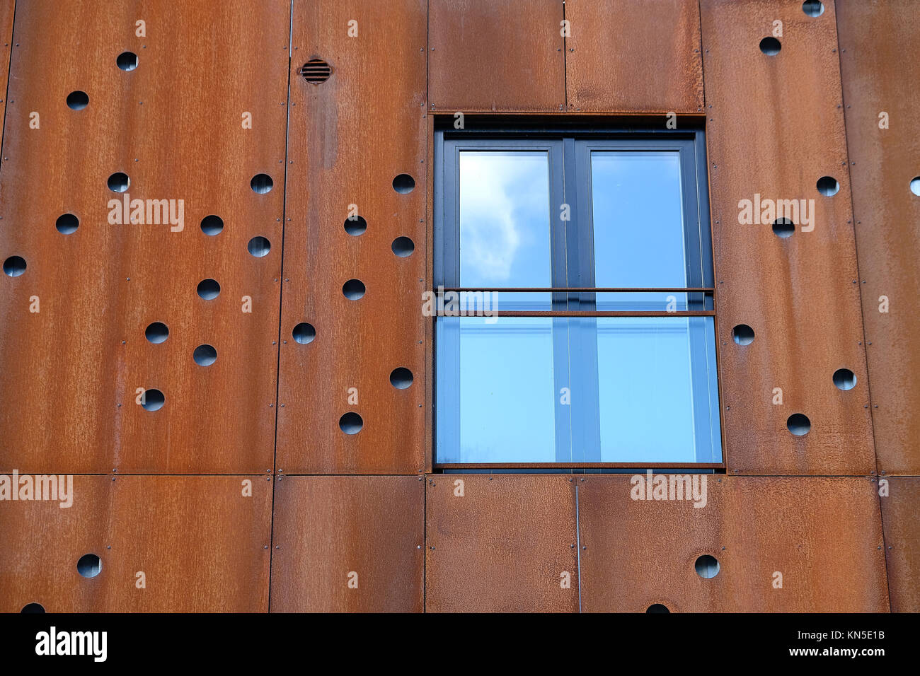 Closeup of window with french balcony in building facade with rusty metal plates with round holes - Stock Image