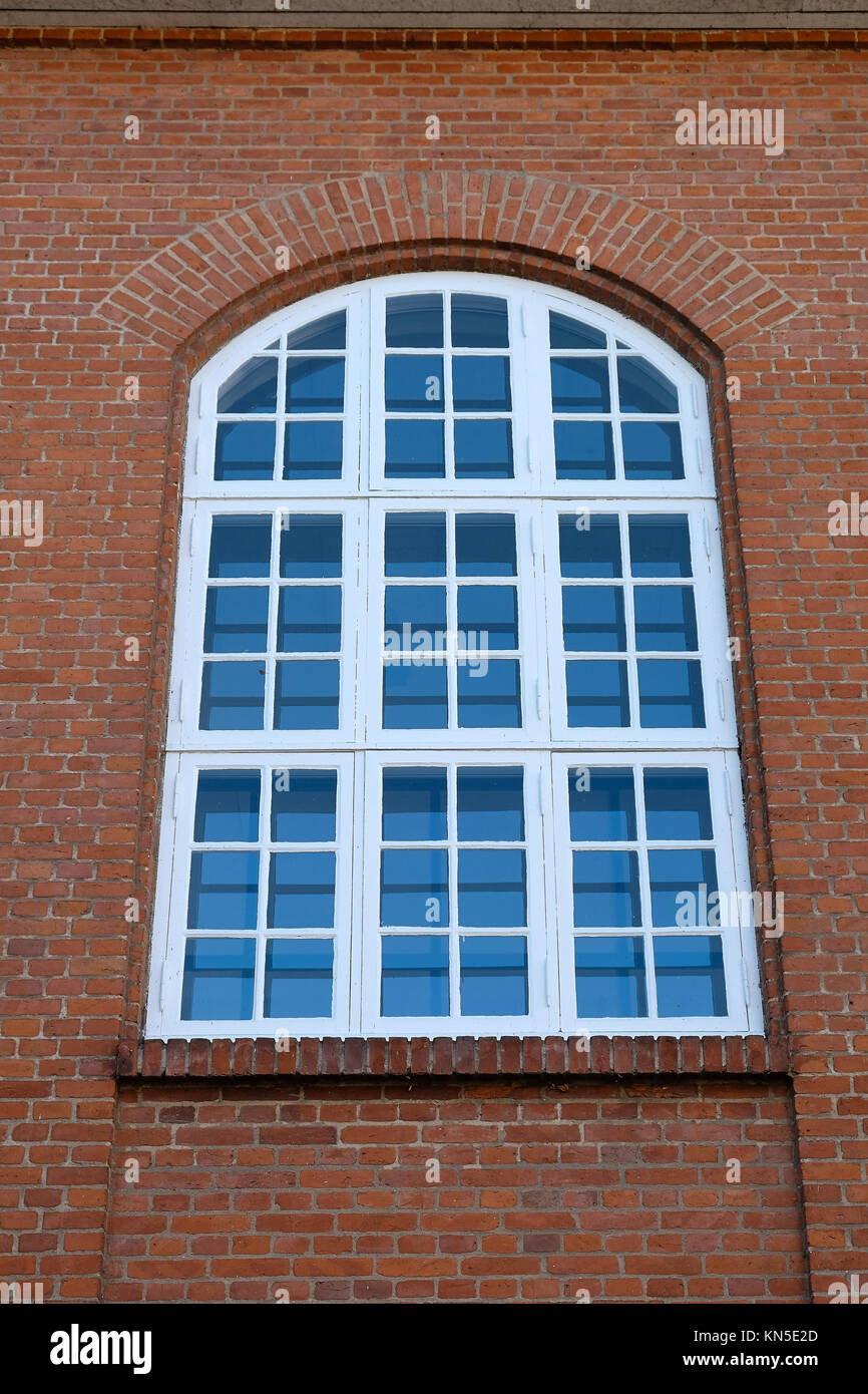 Big tall old white painted wood window with an arched top in a red brick facade - Stock Image