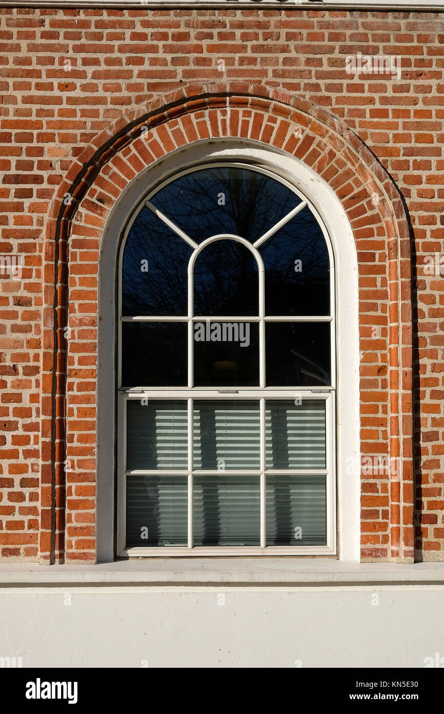 Tall rounded format metal barn style window with designed glazing pattern, in a red brick facade - Stock Image