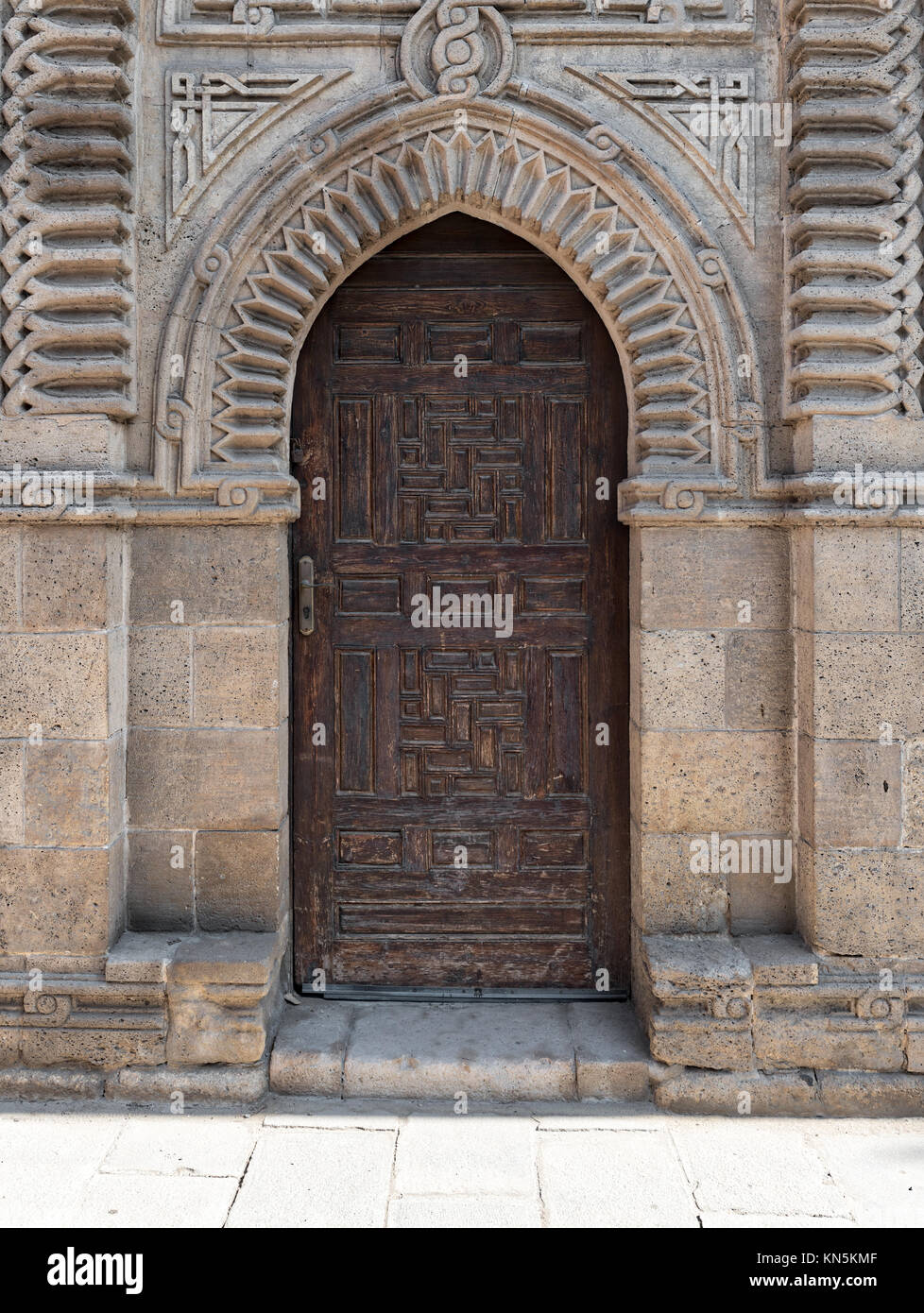 Grunge wooden ornate aged vaulted arched door on exterior decorated stone bricks wall at Manial Palace of prince - Stock Image