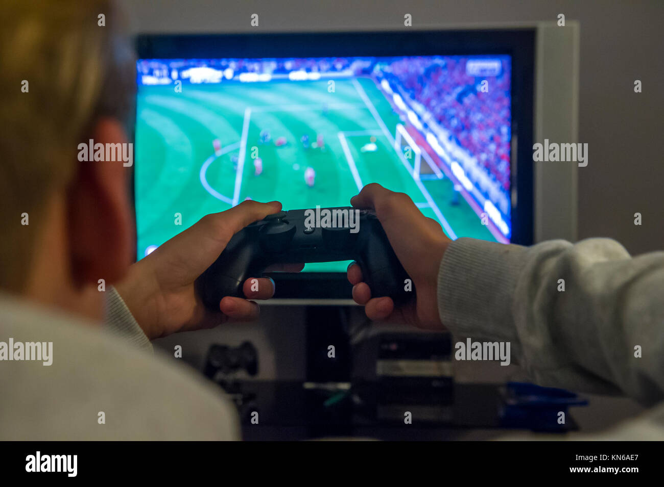 A boy plays a football game on his playstation console - Stock Image