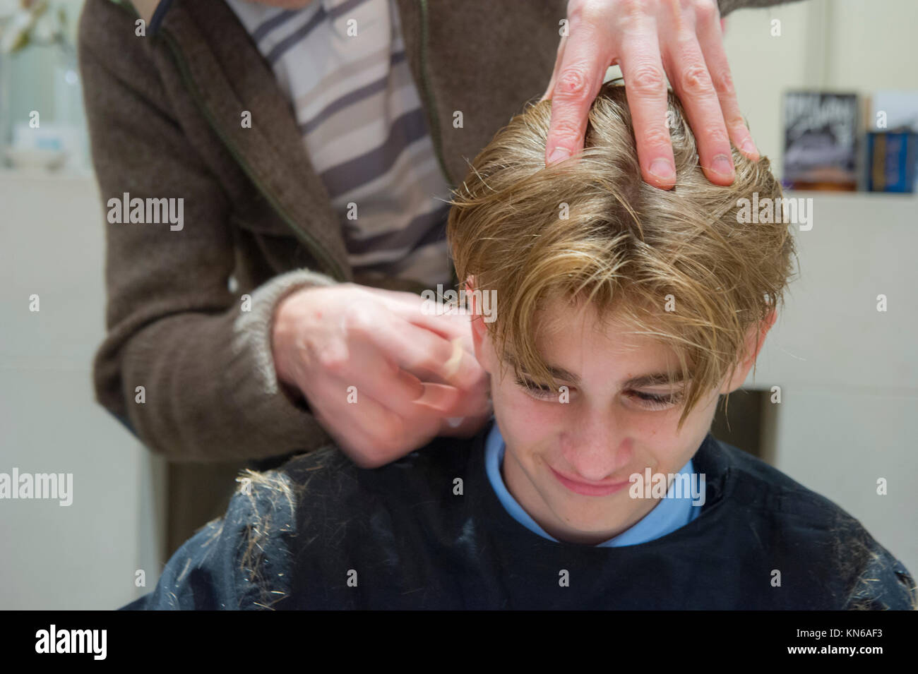 A teenage boy has his hair cut - Stock Image