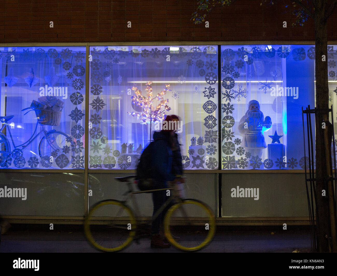 A silhouette of someone looking in to the window of a Christmas display - Stock Image