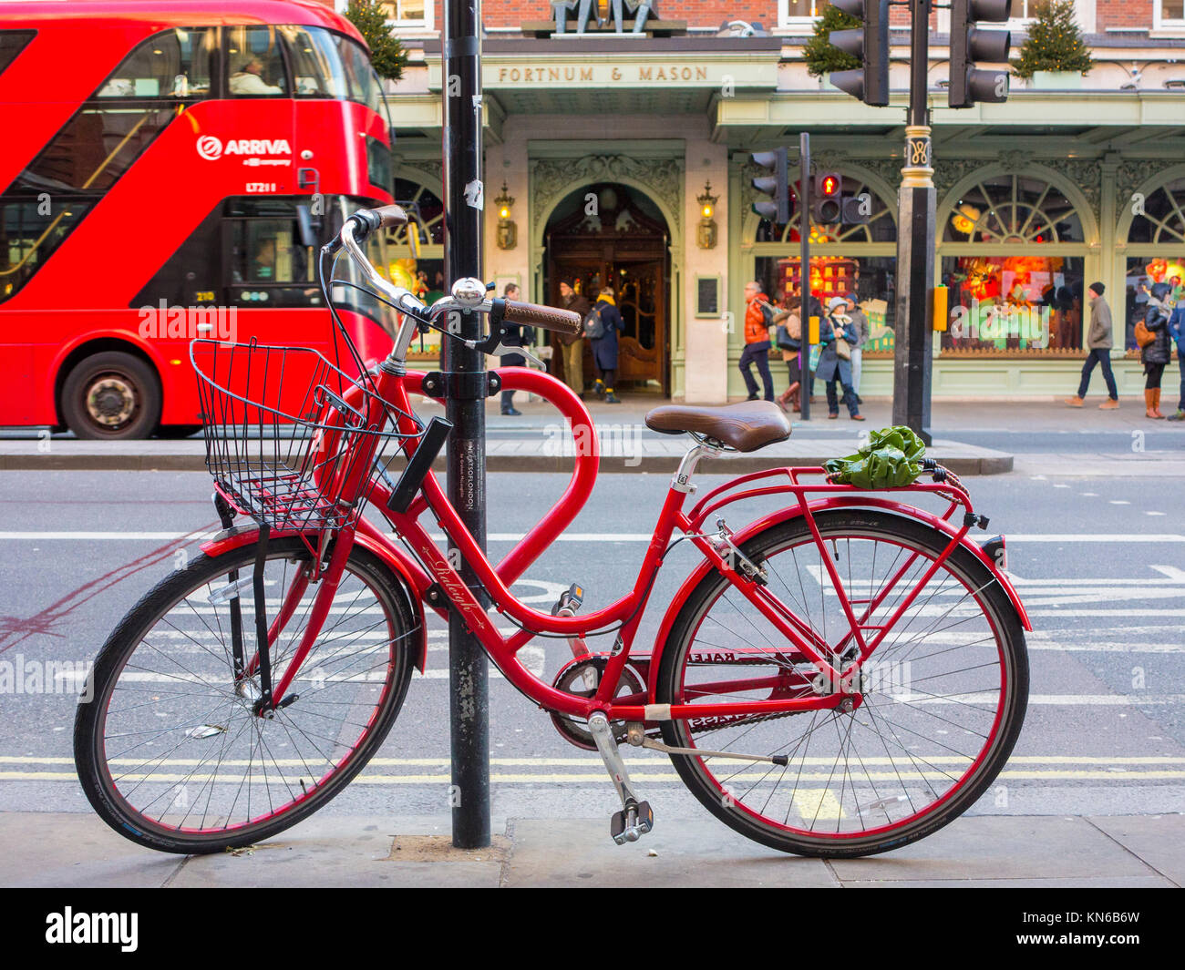 A smart red bicycle parked on Piccadilly outside Fortnum & Masons - Stock Image