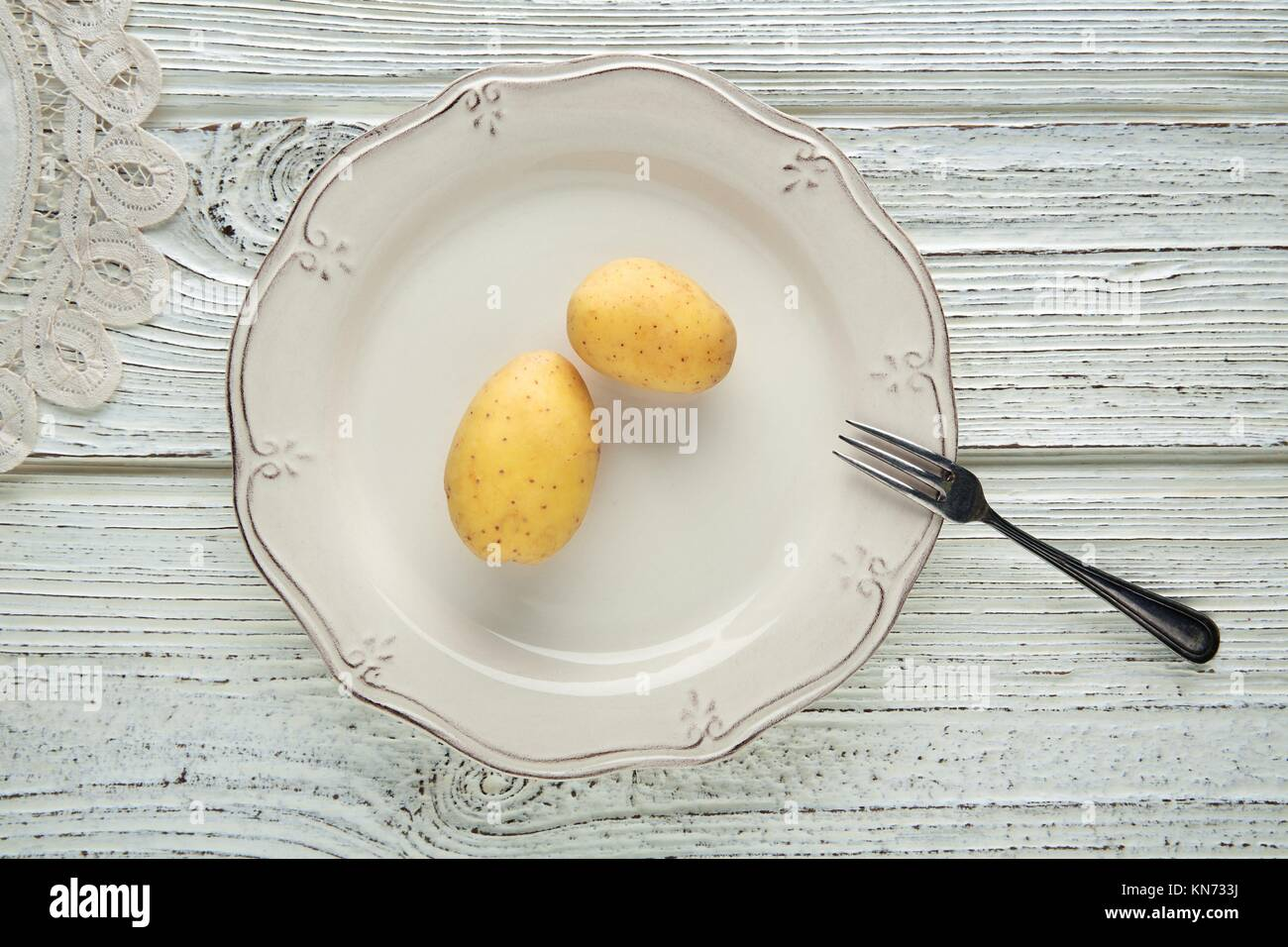 potatoes in white plate minimalist concept of raw vegetarian food. - Stock Image